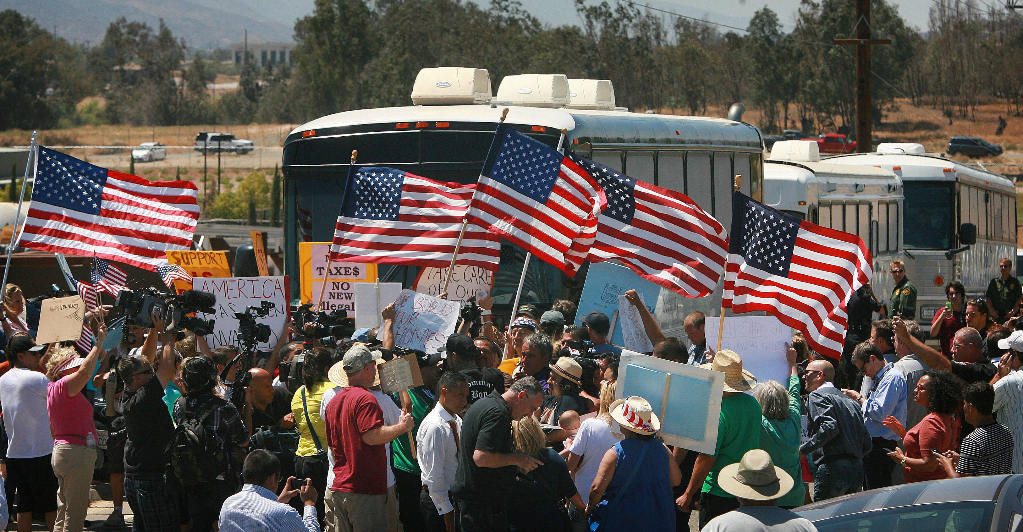 Protesters turn back three buses carrying 140 immigrants as they attempt to enter the U.S. Border Patrol station for processing on Tuesday in Murrieta, Calif.