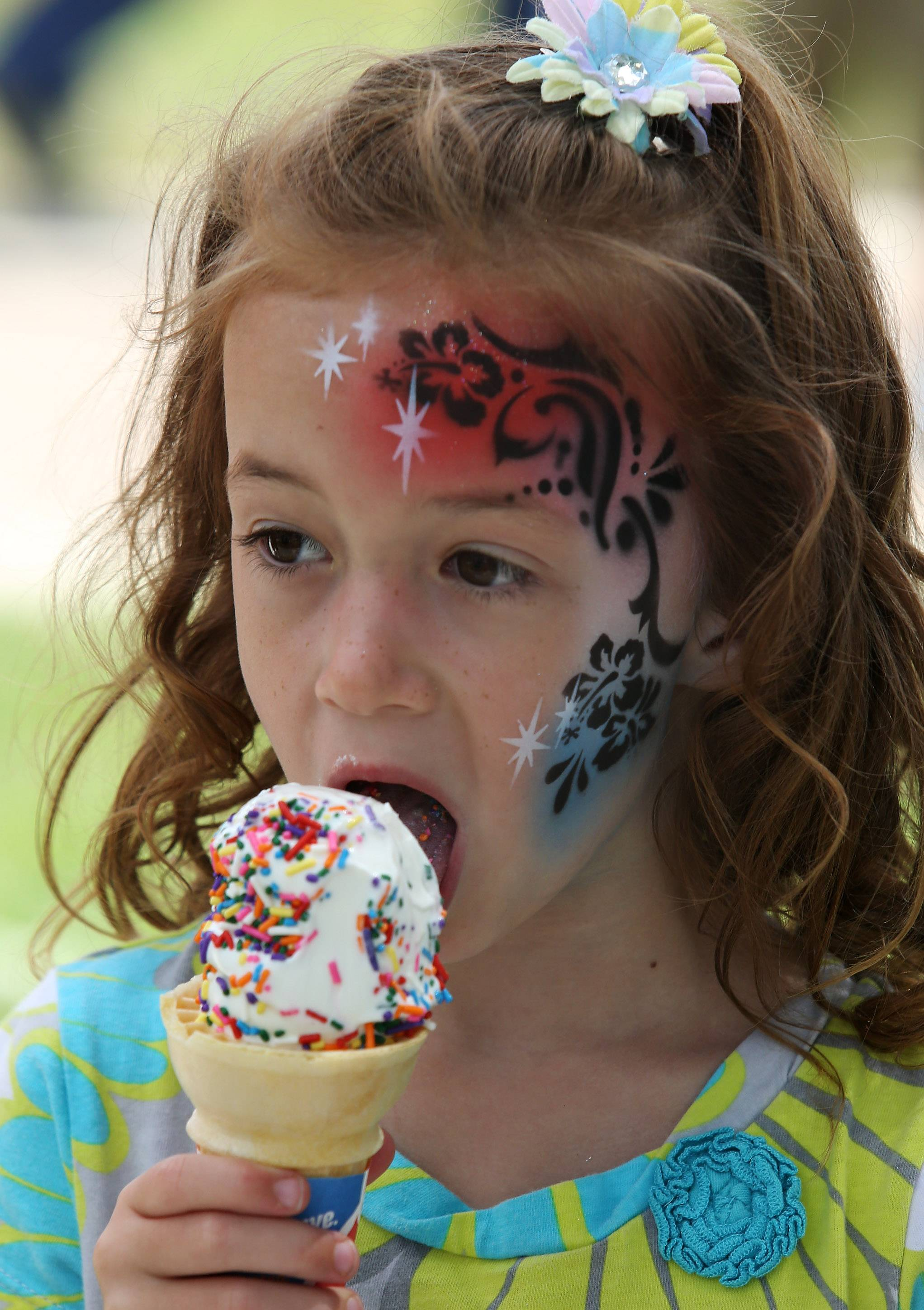 Six-year-old Kate Elliott of Mundelein eats ice cream Thursday after having her face painted by Allison Halver of Just For Fun during the first day of Mundelein Community Days at Kracklauer Park. The festival runs through Sunday, featuring music, food tents, games, and carnival rides.