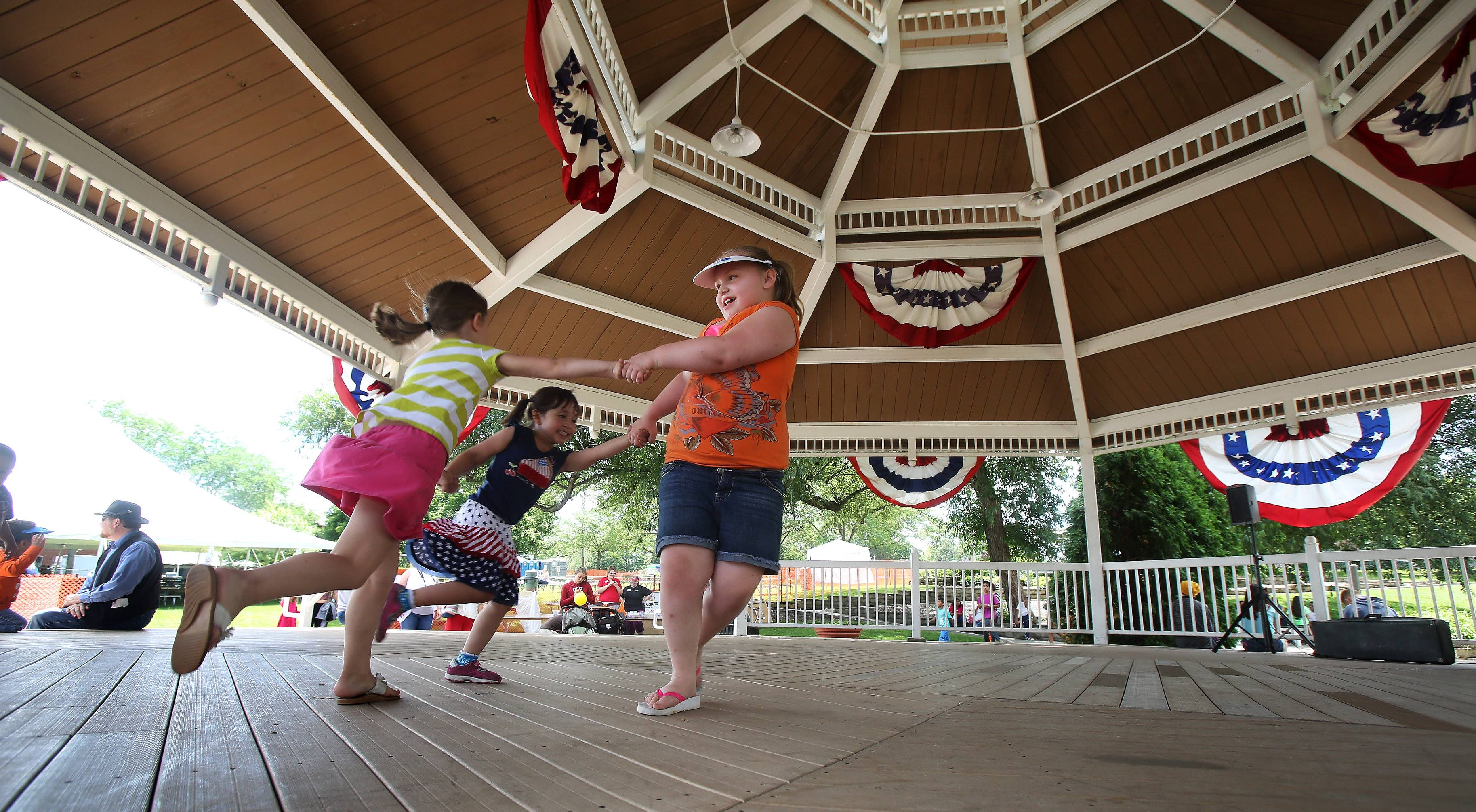 Ava Letendre, 4, left, Elisa Portilla-Dehn, 4, and Violet Caldwell, 8, dance on the stage of the gazebo Thursday during the first day of Mundelein Community Days at Kracklauer Park. The festival features music, food tents, games, and carnival rides.