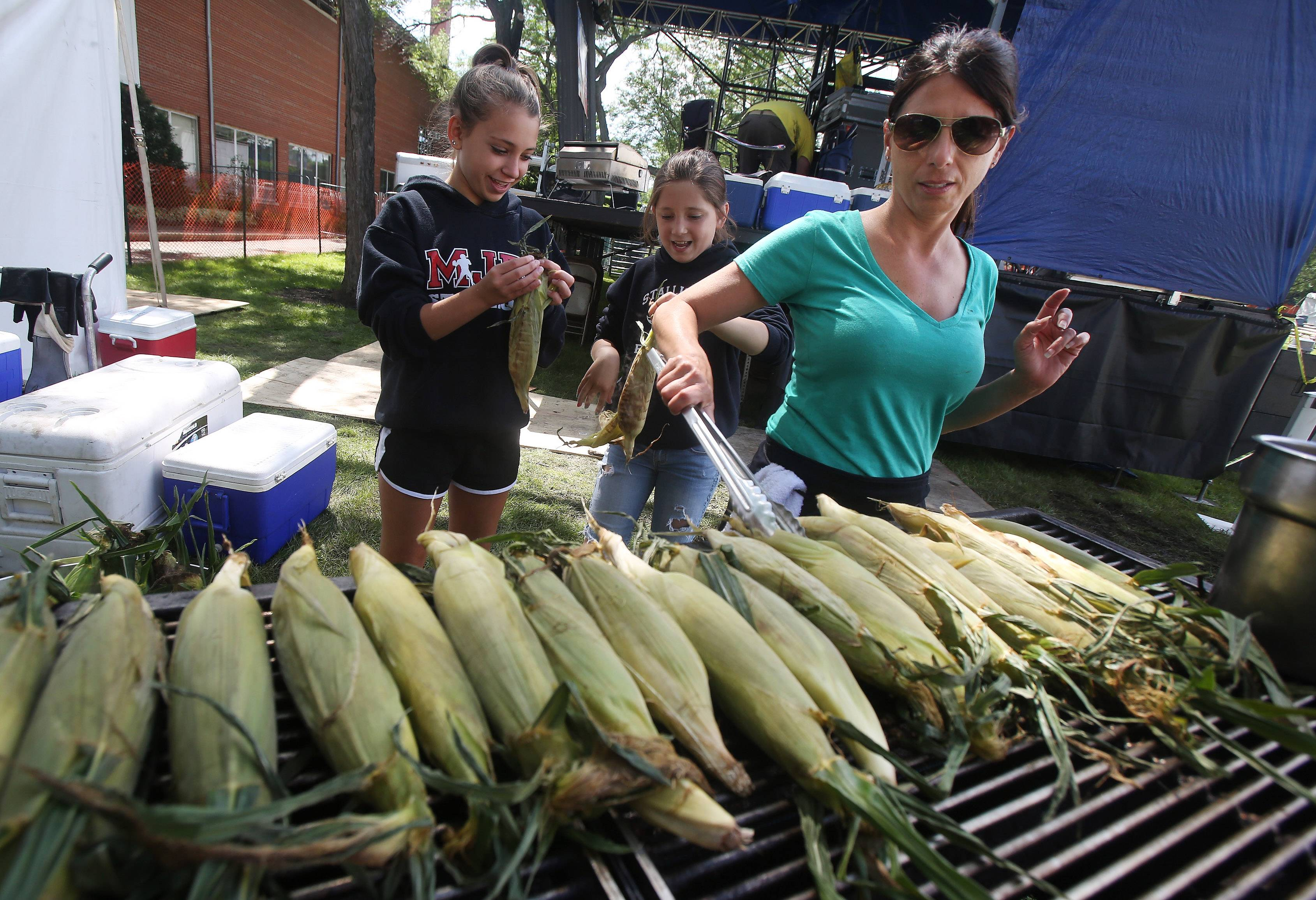 Michelle Coutre of Mundelein roasts corn with her daughters, Lily, 10, and Olivia, 13, at the Brother's BBQ tent Thursday during the first day of Mundelein Community Days at Kracklauer Park. The festival runs through Sunday, featuring music, food tents, games, and carnival rides.