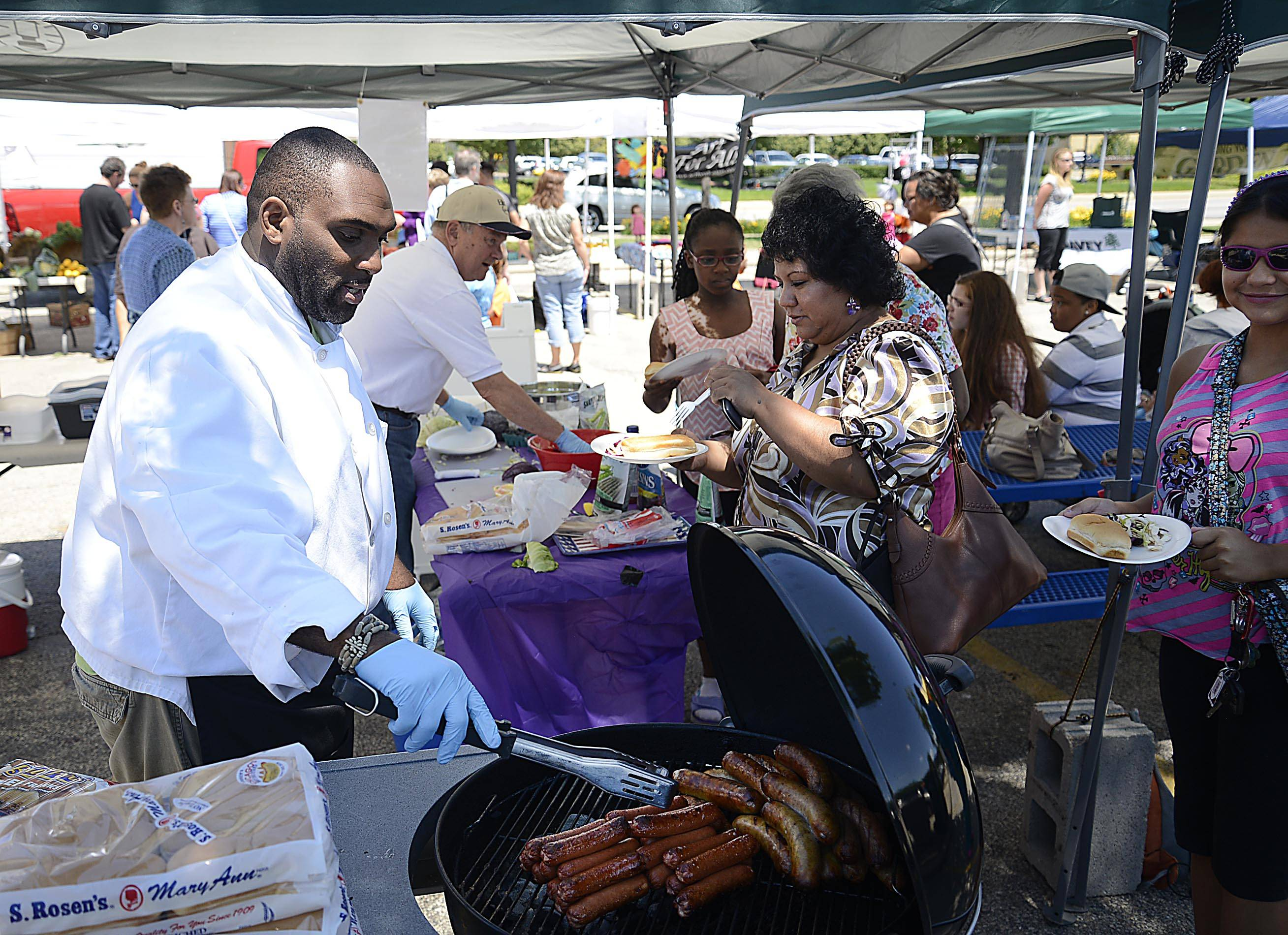 Chef Quincy Owens reaches for grilled hot dogs as he and Elgin Mayor David Kaptain make healthy side dishes for kids Thursday at the Downtown Elgin Harvest Market.
