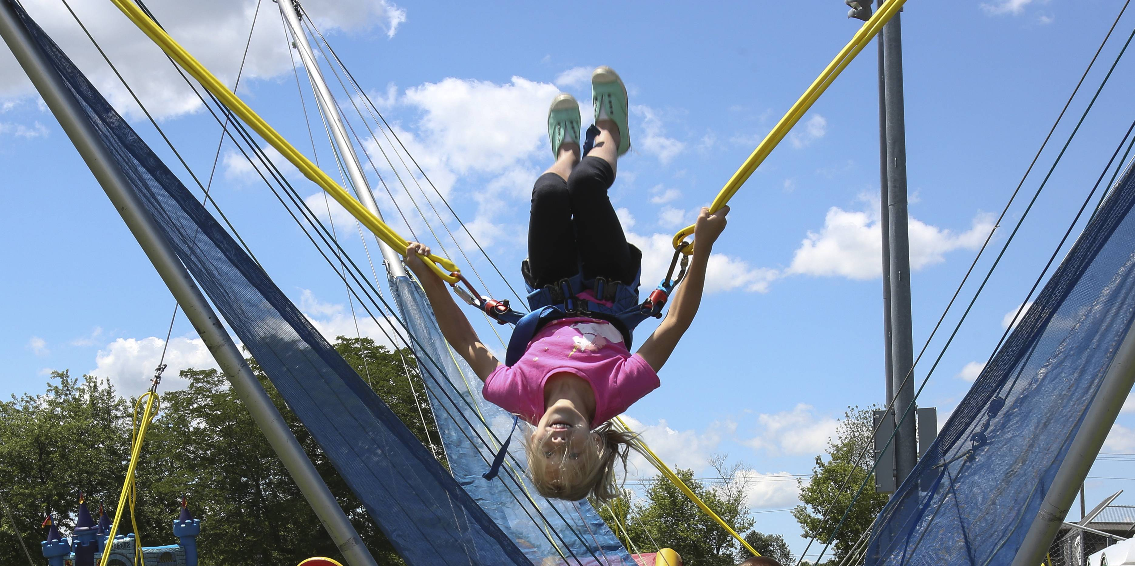 Lauren Jaskier, 7, of Lombard, tries out her gymnastics skills Thursday on the Euro Bungee during the opening day of the Naperville Exchange Club's Ribfest.