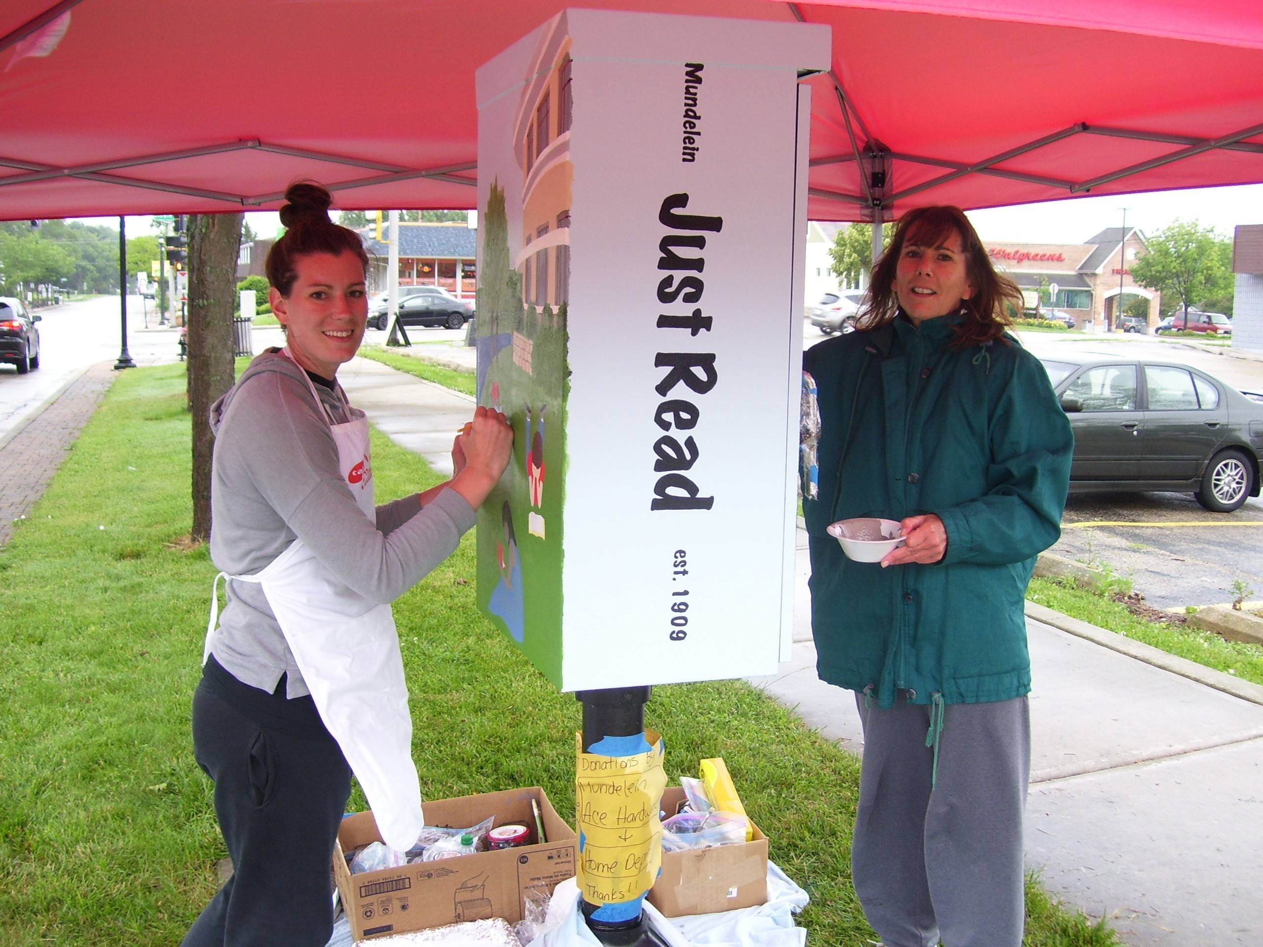 Artist Mary Hecht, right, and daughter Kristin Cropper paint a utility box on north Seymour Avenue in Mundelein as part of a public art project. The painting depicts children reading outside the Fremont Public Library and at a park.