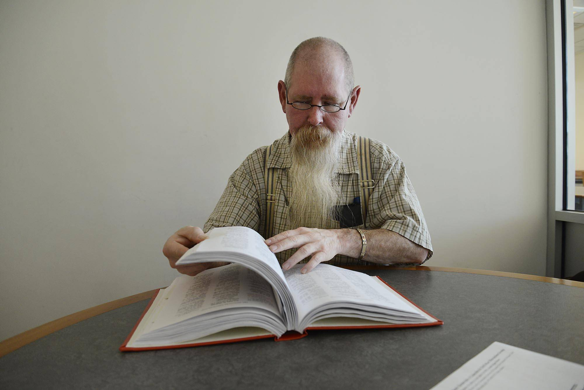 "Ken Gough flips through his book at the Gail Borden Public Library in Elgin. He is a Civil War historian who spent nine years researching Elgin soldiers and has published a book called ""Elgin, Illinois Soldiers of the Civil War."" He updates the book as new information is found."