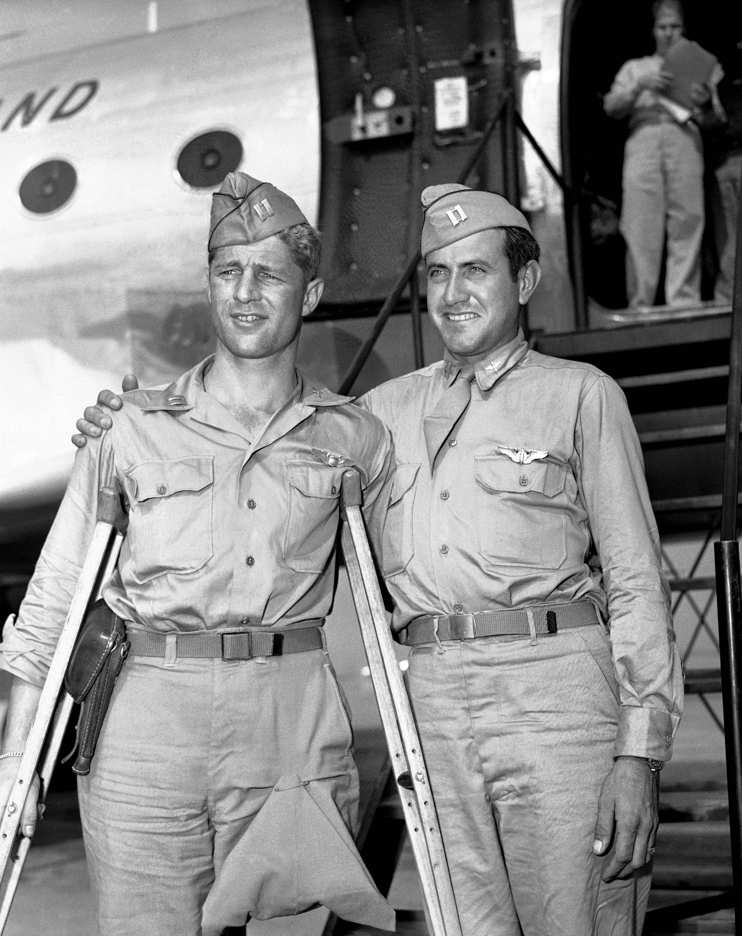 Capt. Louis Zamperini, right, former track star who was adrift 47 days in Pacific after bombing mission against the Japanese and presumed dead, stands with Capt. Fred Garrett. Both were prisoners of war. Zamperini died Wednesday, July 2, 2014. He was 97.