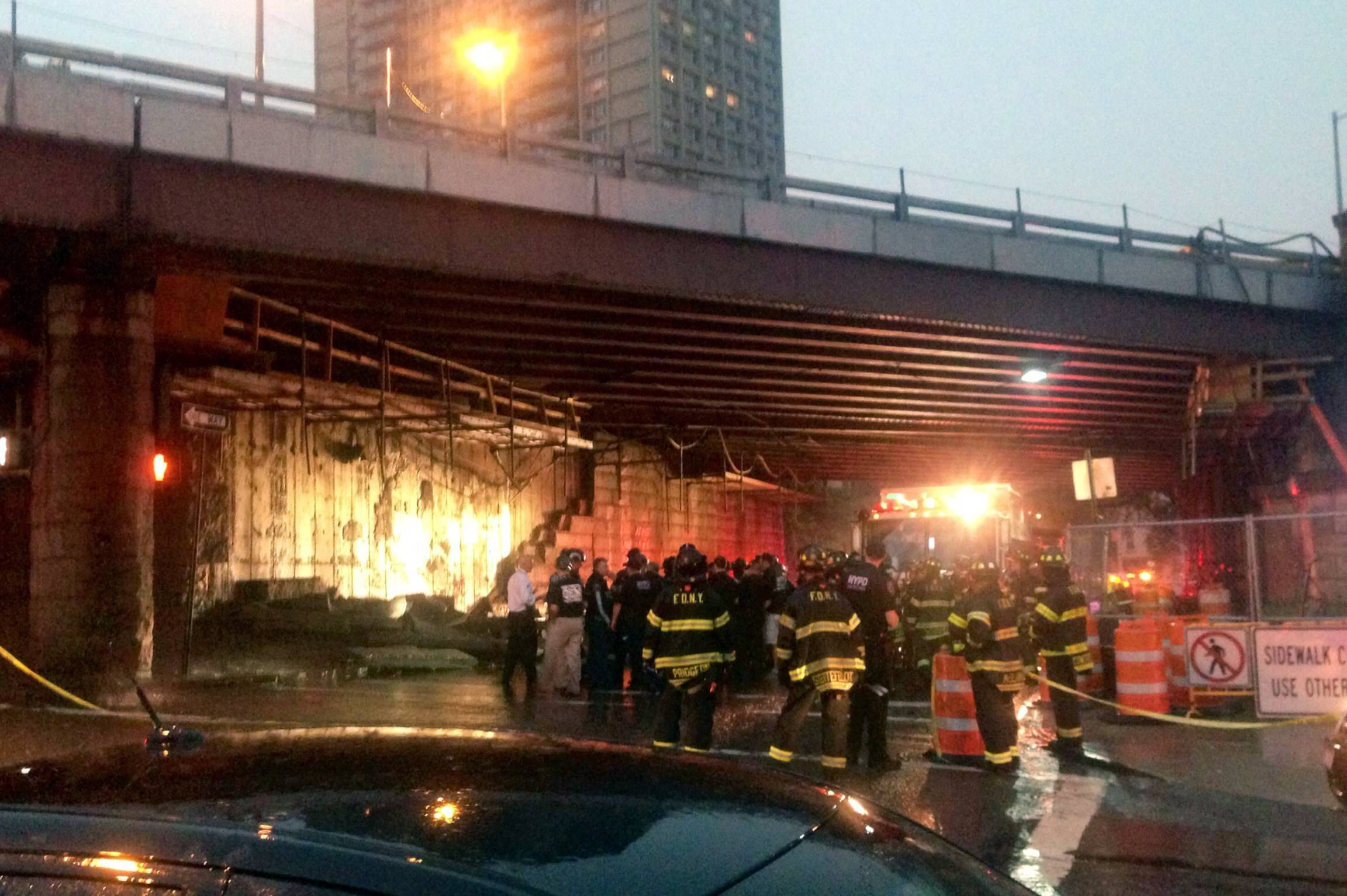 Emergency personal near a section of the facade Wednesday inside an underpass of the Brooklyn Bridge after it had collapsed. A fire department spokesman says five people were injured.