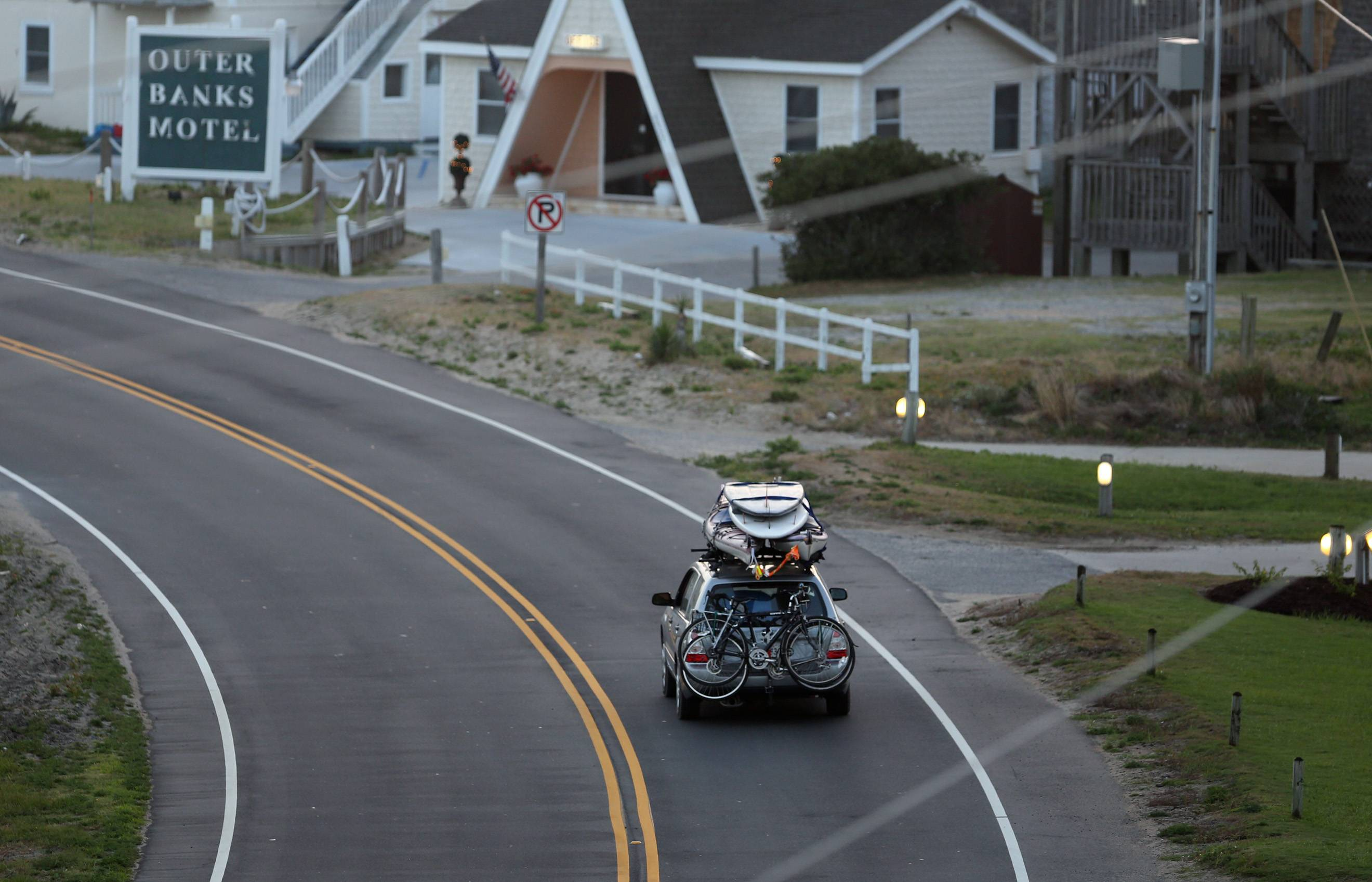A car loaded down with bikes, kayaks and surfboards heads north on NC 12 through Buxton on Hatteras Island, N.C., at dawn on Thursday. The island is under a mandatory evacuation order because of approaching Hurricane Arthur.