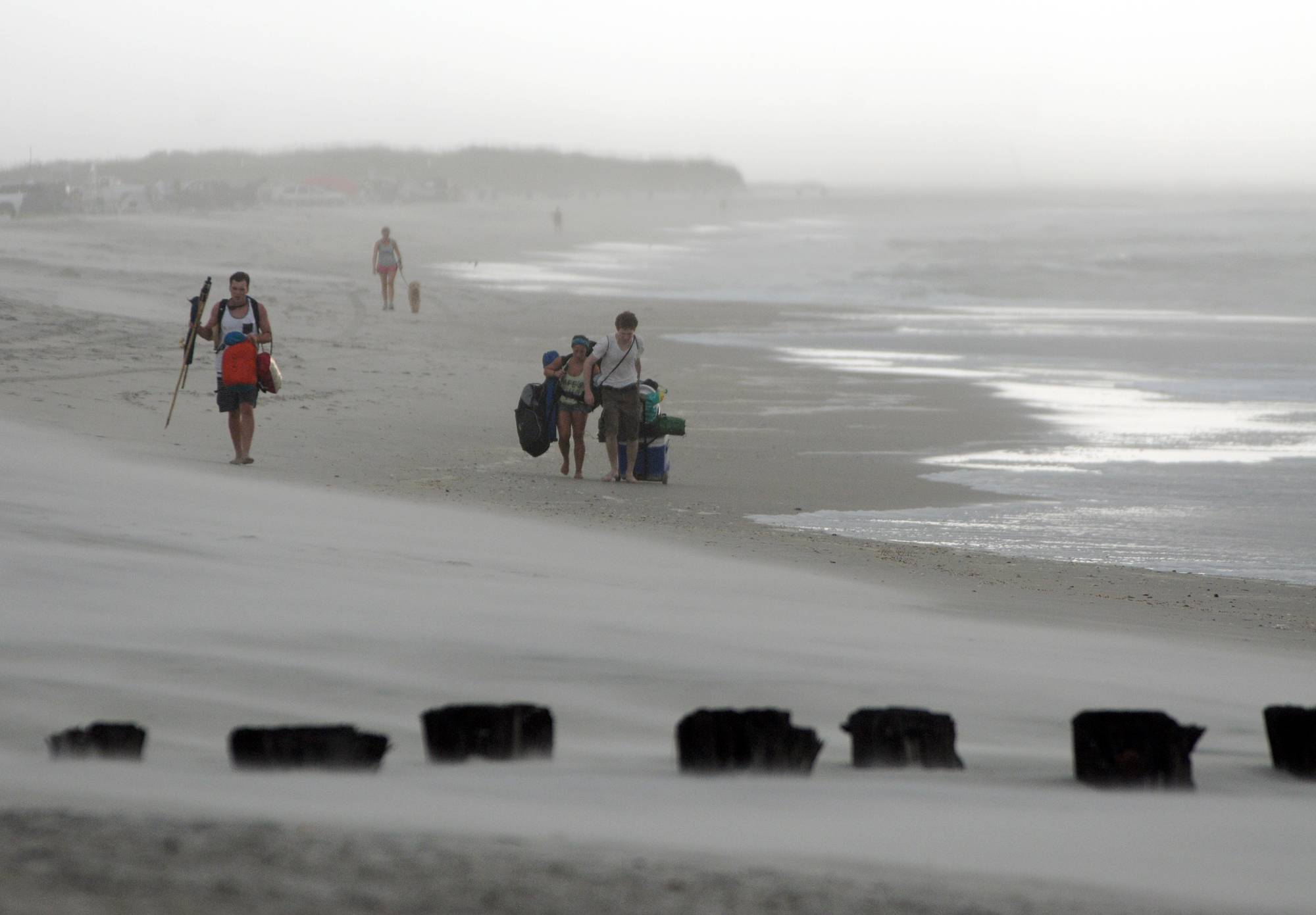 Clouds and rains move in as beachgoers leave Freeman Park at the north end of Carolina Beach, N.C., Thursday. Residents along the coast of North Carolina are bracing for the arrival of the Hurricane Arthur, which threatens to give the state a glancing blow on Independence Day.
