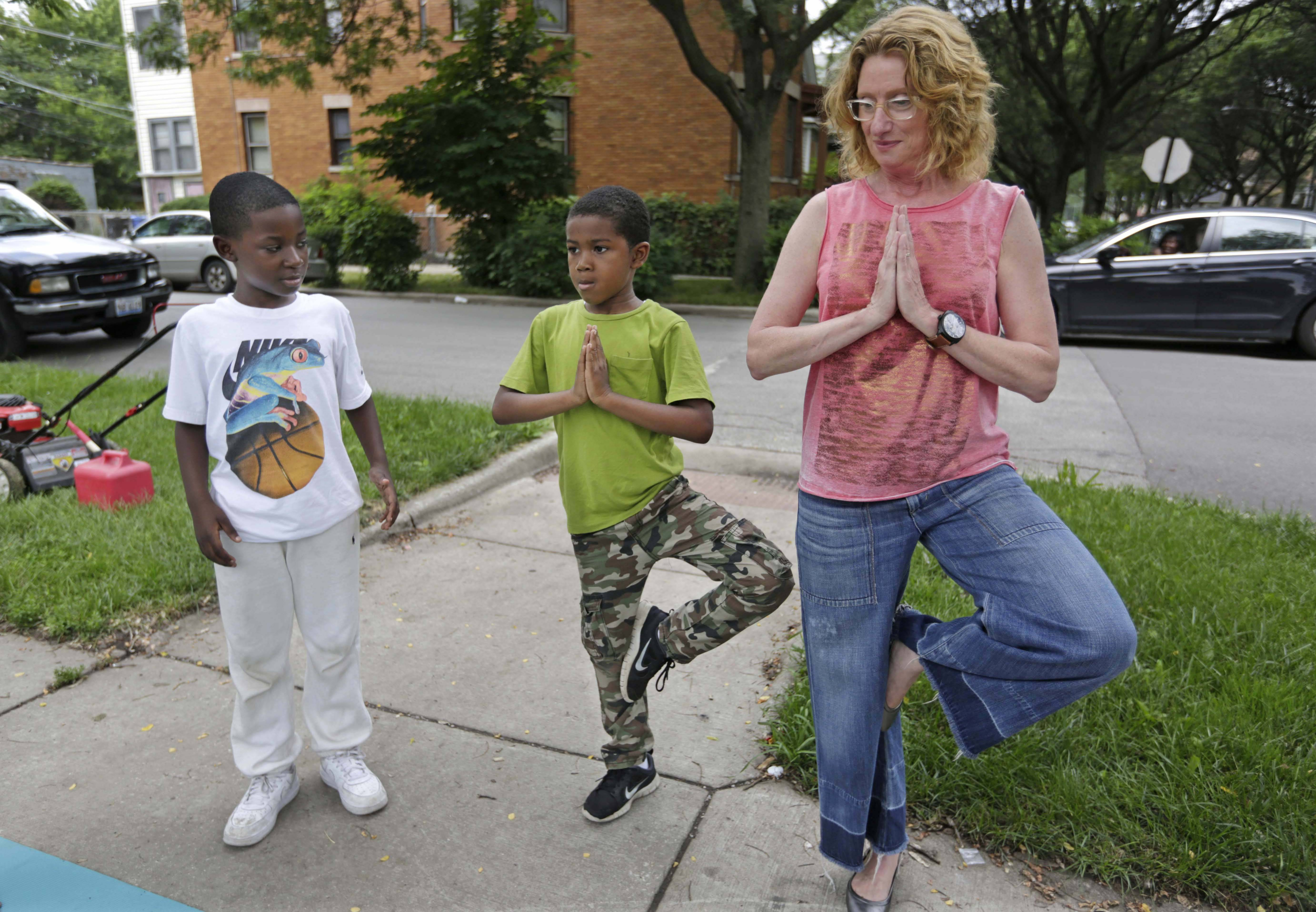 'I Grow Chicago' co-founder Robbin Carroll, right, practices with Sanchez Yerger, left, and Brendan Johnson, before they take part in a yoga class on the often violent streets of Chicago's Englewood neighborhood in Chicago. The hope is that yoga's meditative focus will help cooler heads prevail the next time violence or vengeance looms.