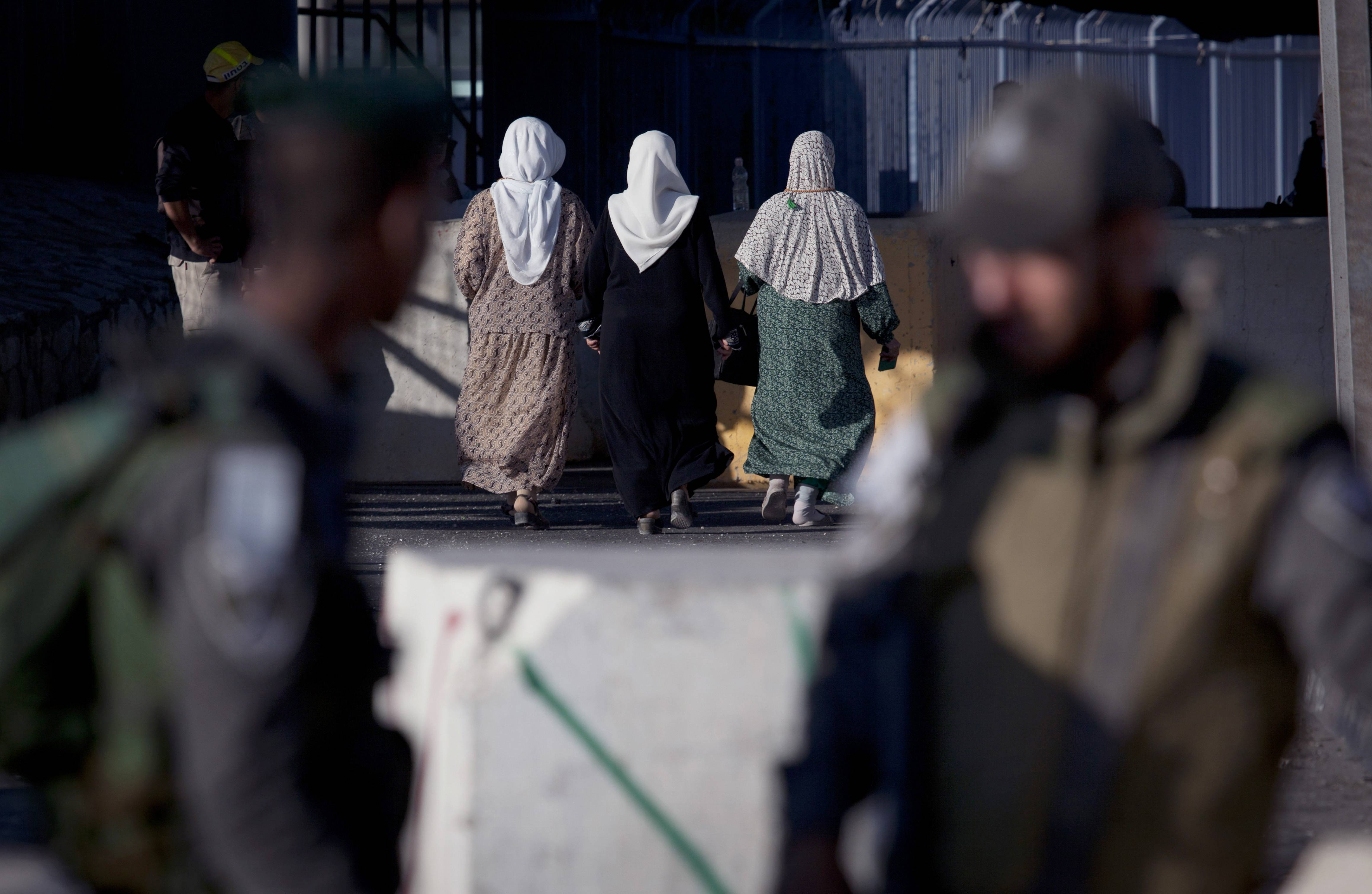 Palestinian women walk Friday through the Qalandia security checkpoint on their way to Jerusalem, behind two Israeli border guards officers, on the outskirts of the West Bank city of Ramallah.
