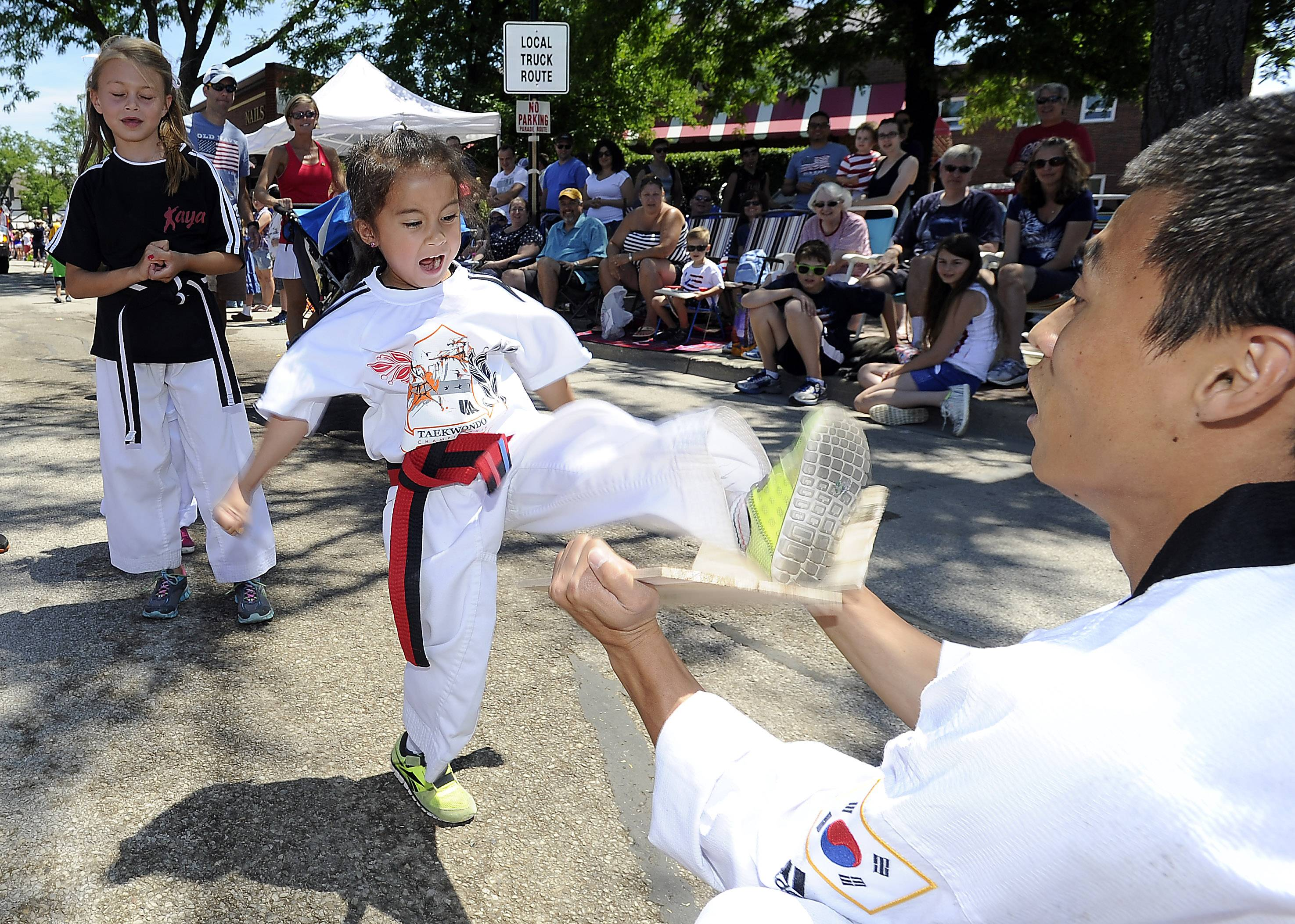 Caylle Del Boccio, 5, of Mount Prospect breaks boards for the Mount Prospect parade audience as part of her training from Kaya Martial Arts of Arlington Heights.