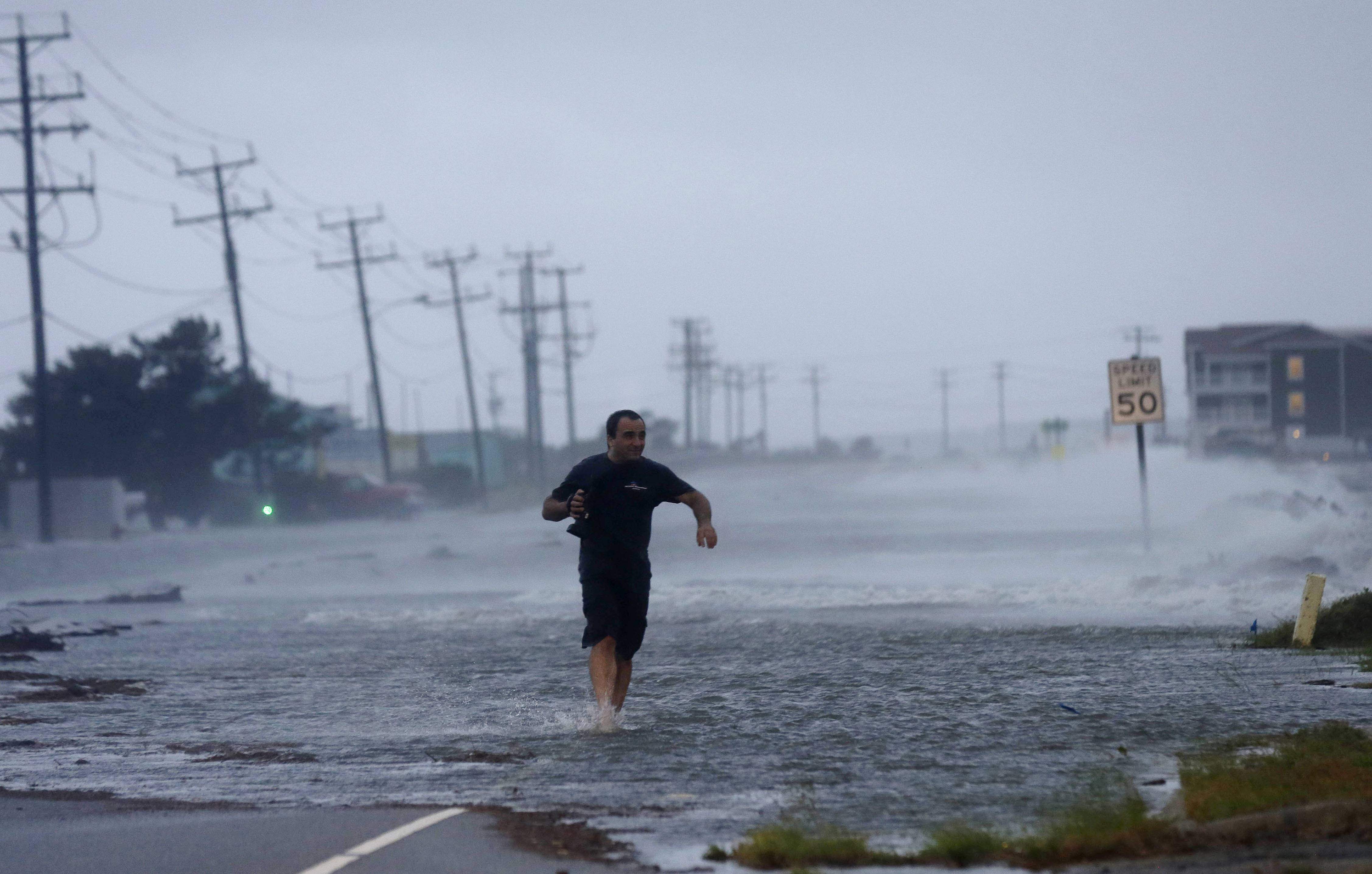 A man crosses a flooded Highway 64 as wind pushes water over the road as Hurricane Arthur passes through Nags Head, N.C., Friday, July 4, 2014.