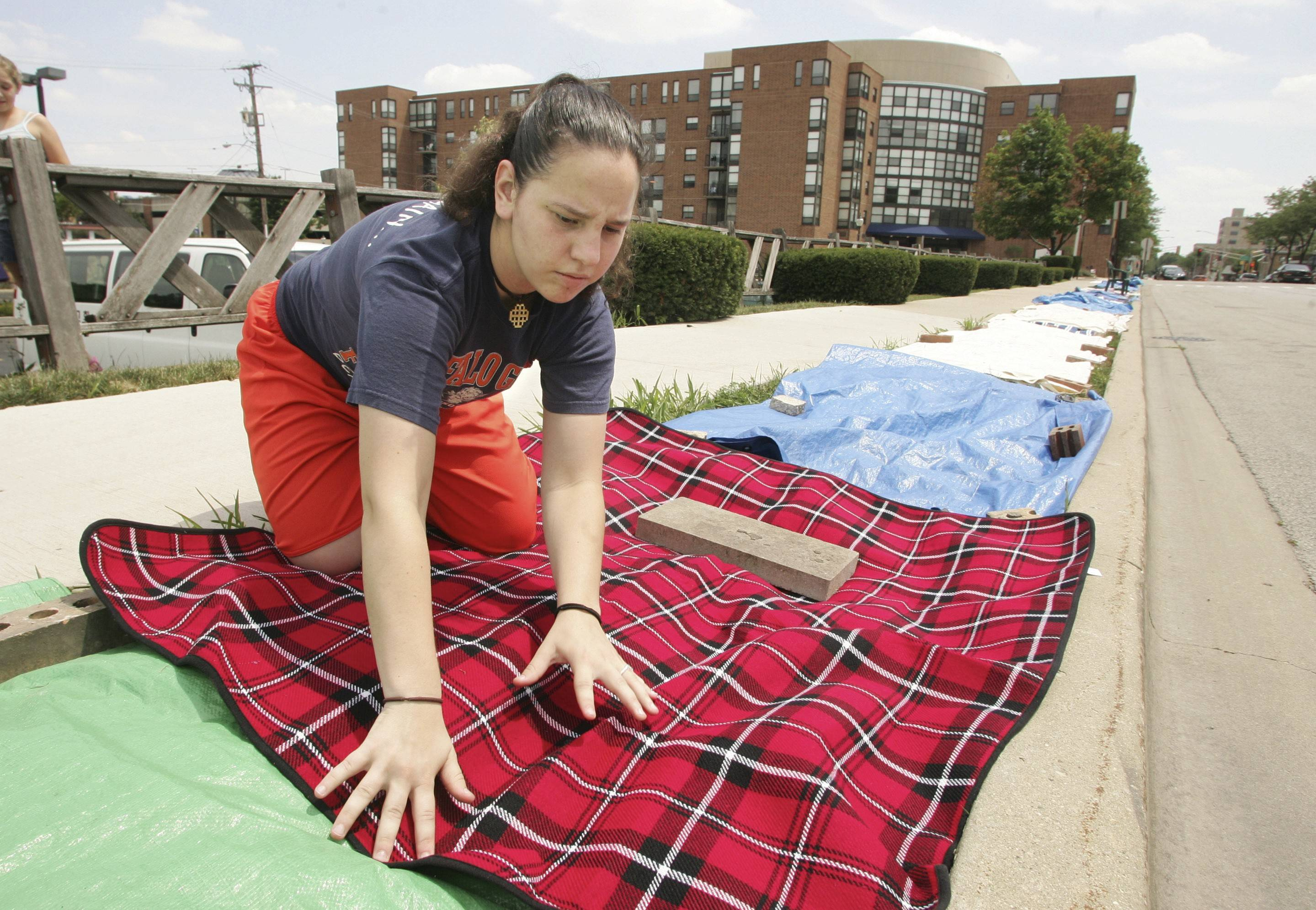 A woman lays down a blanket alongside hundreds of other blankets, plastic tarps, and chairs placed along Dunton Avenue to reserve places to watch the Fourth of July parade in Arlington Heights.