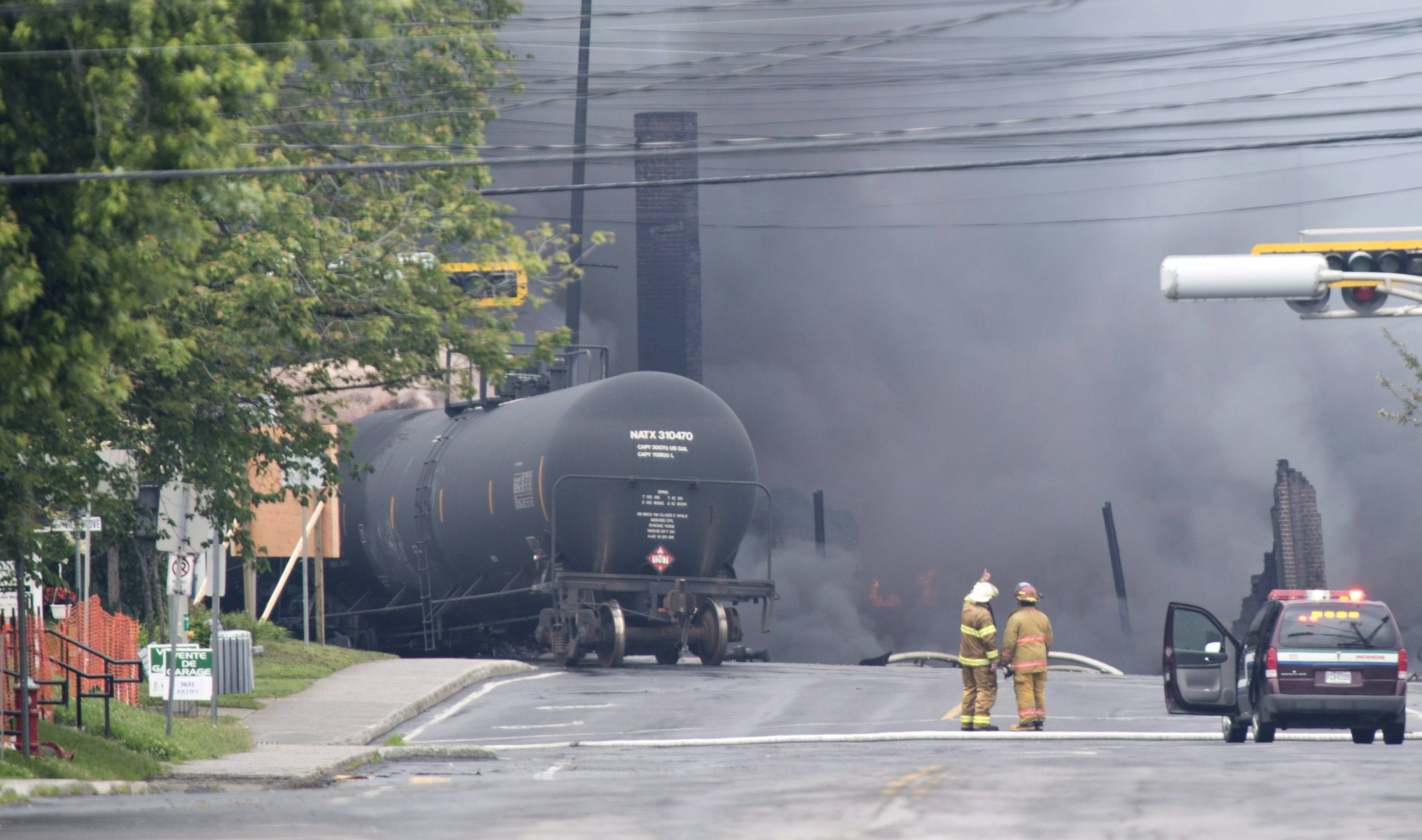 Smoke rises from railway cars carrying crude oil after derailing in downtown Lac-Megantic, Quebec. Lac-Megantic still struggles to recover as it marks the disaster's one-year anniversary.