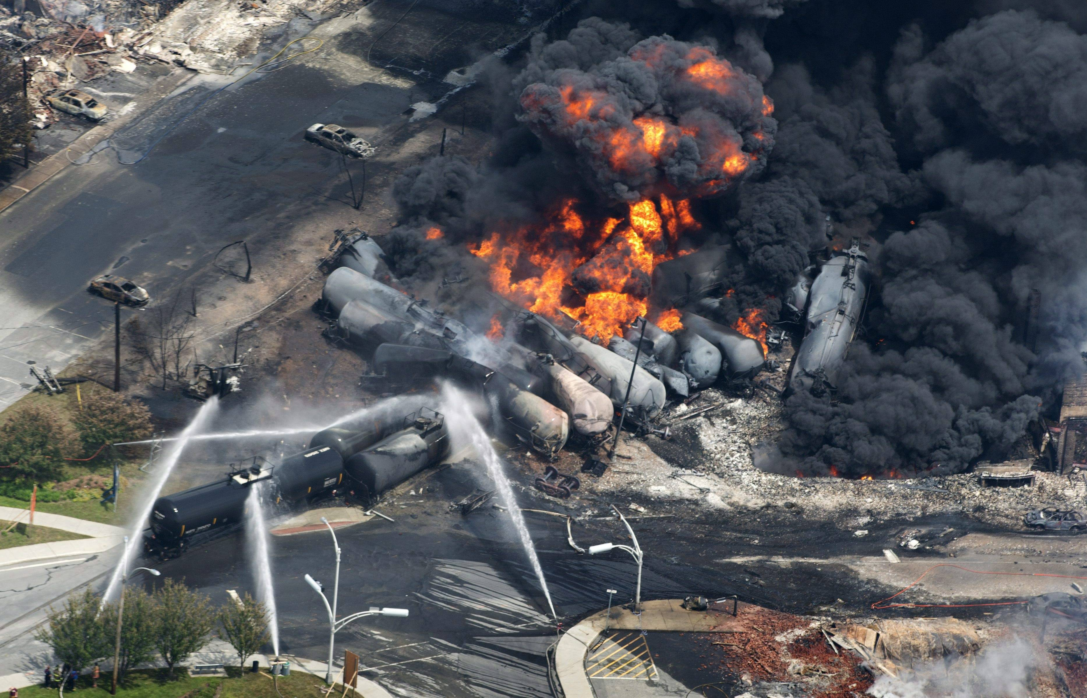 Firefighters douse railway cars carrying crude oil after derailing in downtown Lac Megantic, Quebec.