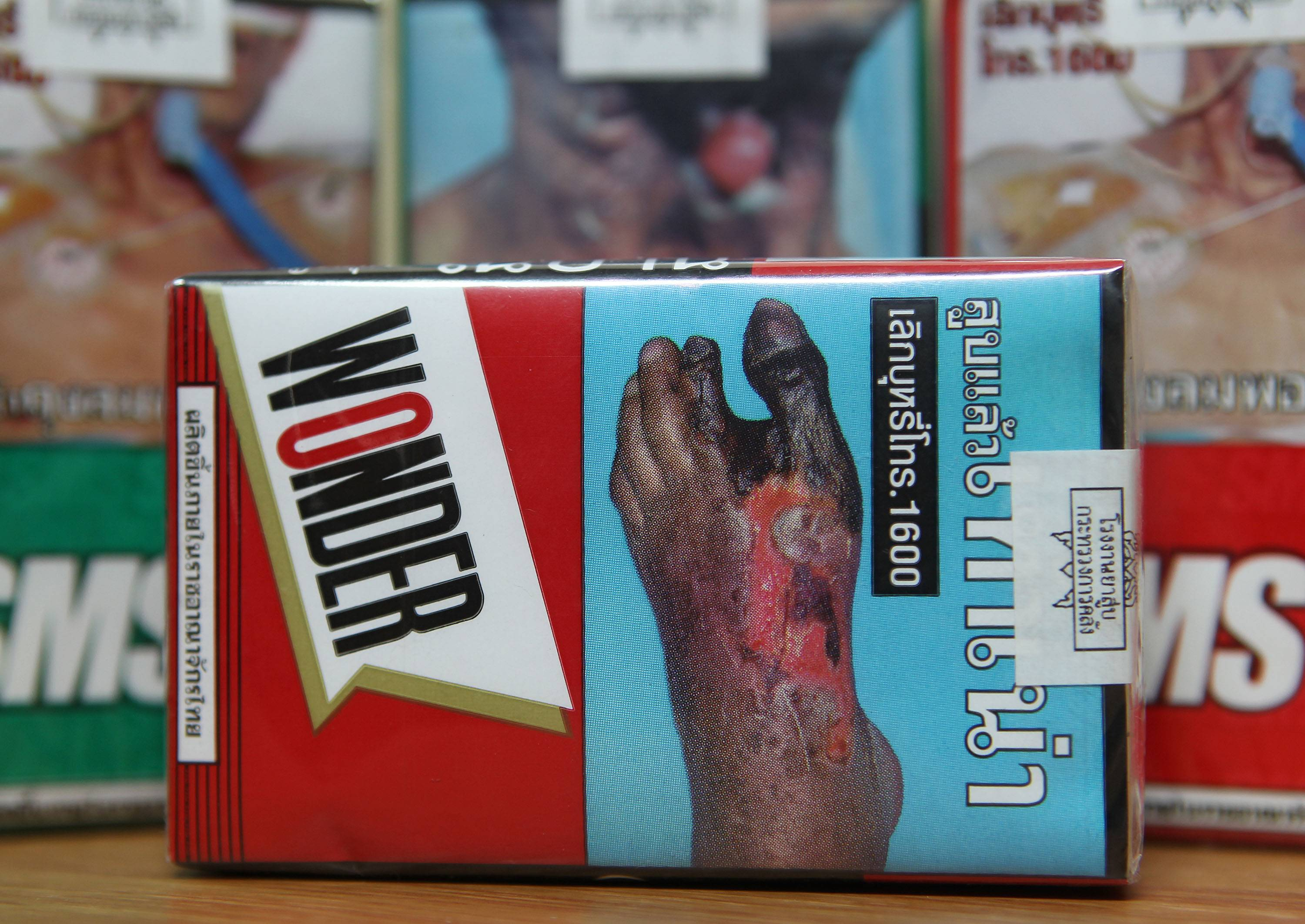 In this June 26, 2013 file photo, the warning signs are printed on the cigarette packets on sale in Bangkok.