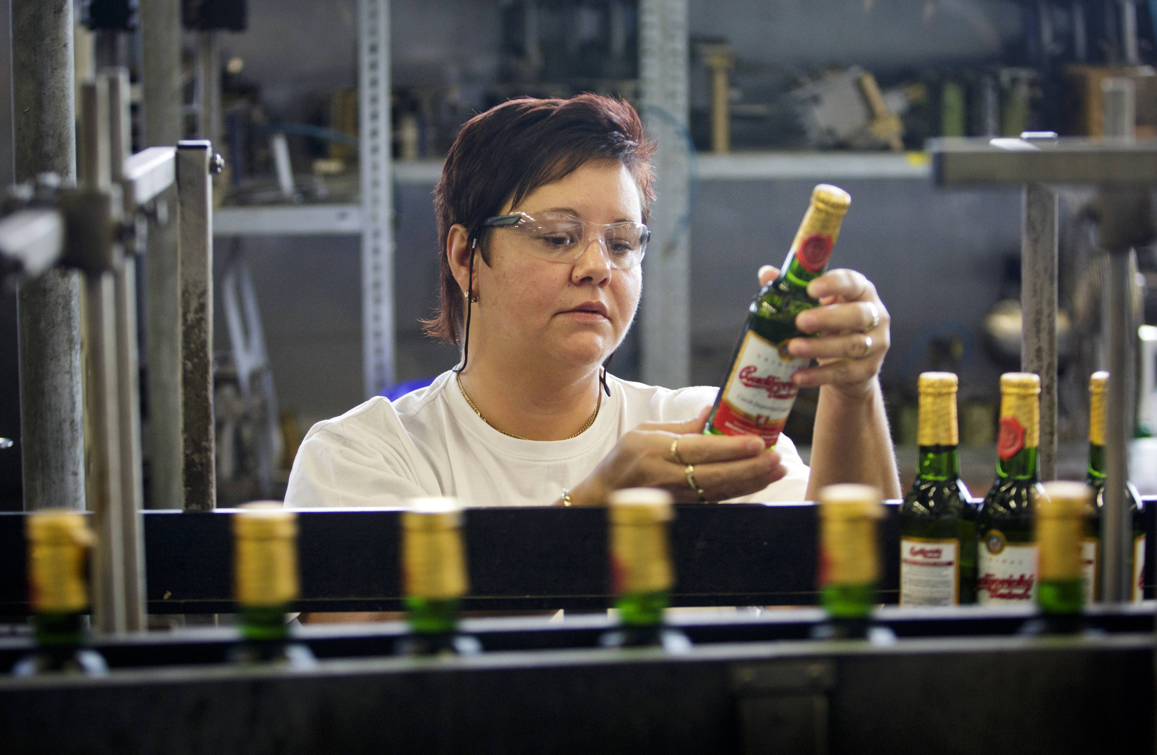 An employee inspects bottles of Budweiser Budvar beer as they pass along the production line in Ceske Budejovicky, Czech Republic. The success of Czech beermakers in finding a foothold in more exotic destinations will depend on how well they address unfamiliar regulations, different drinking habits and low incomes among new consumers, analysts say.