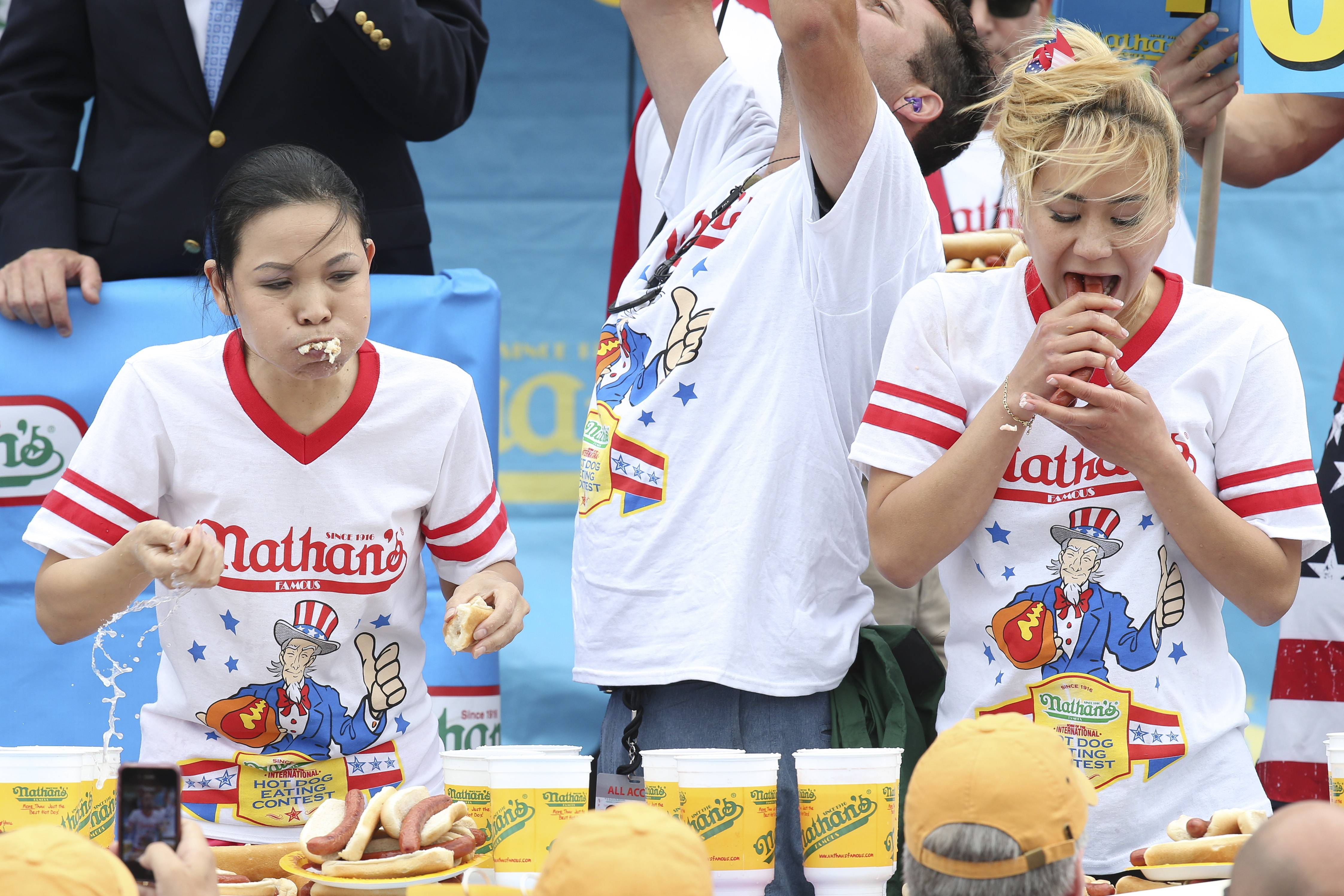 Sonya Thomas, left, and Miki Sudo, right, compete at the Nathan's Famous Fourth of July International Hot Dog Eating contest. Sudo defeated the reigning champion Thomas by eating 34 hot dogs and buns.