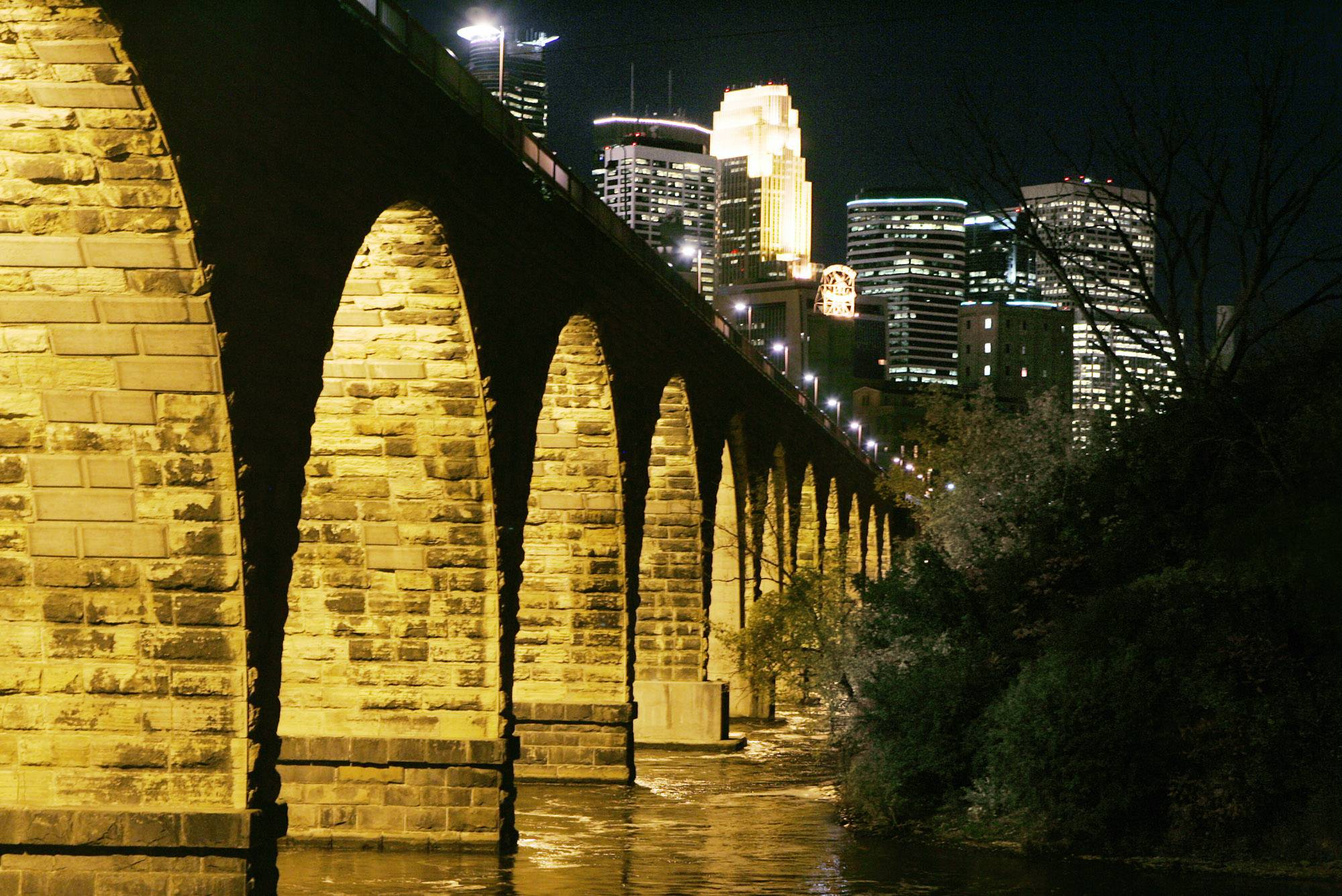 The Minneapolis skyline is illuminated in the background from the historic Stone Arch Bridge over the Mississippi River.