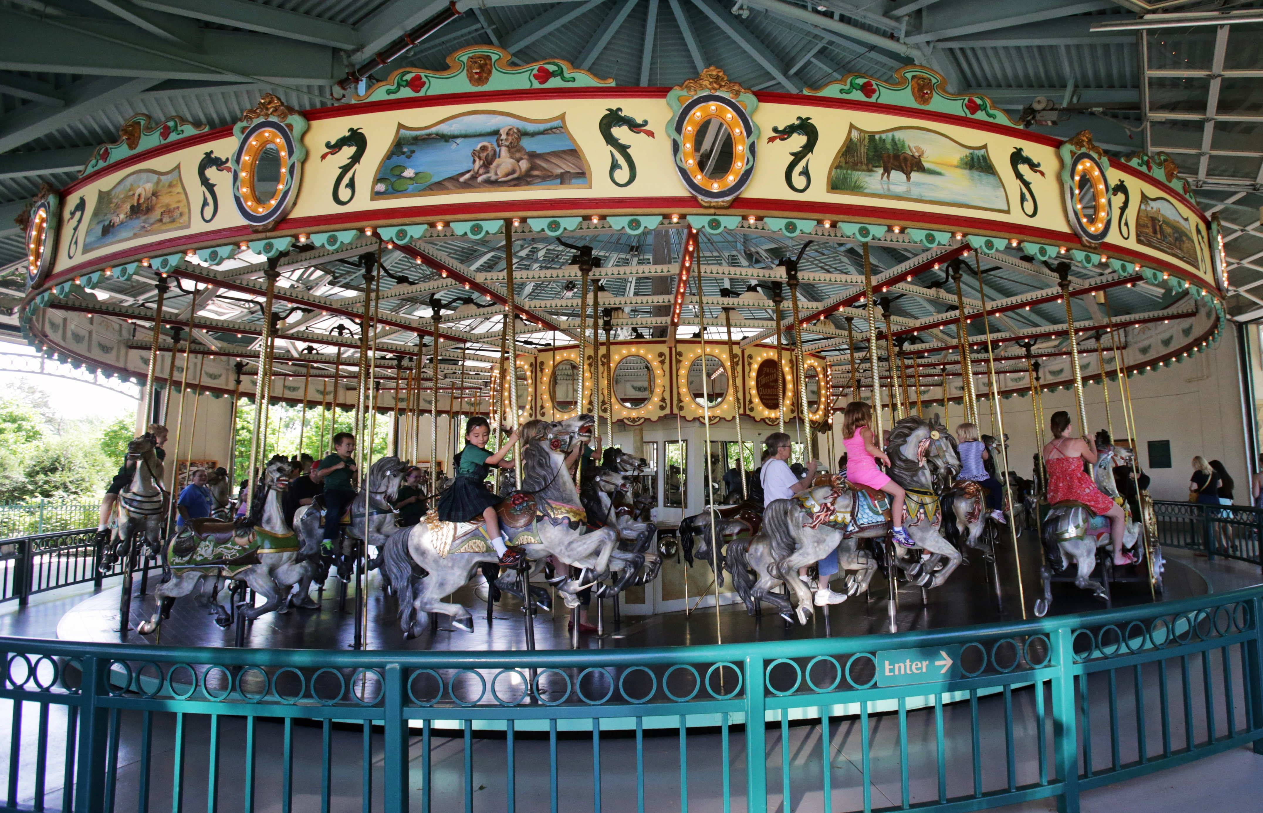Kids and adults ride the 100-year-old Cafesjian's Carousel in the Como Town amusement park in St. Paul, Minn. Parking at the Como Town and adjacent Como Park Zoo and Conservatory is free, but there is a charge to ride the Carousel.