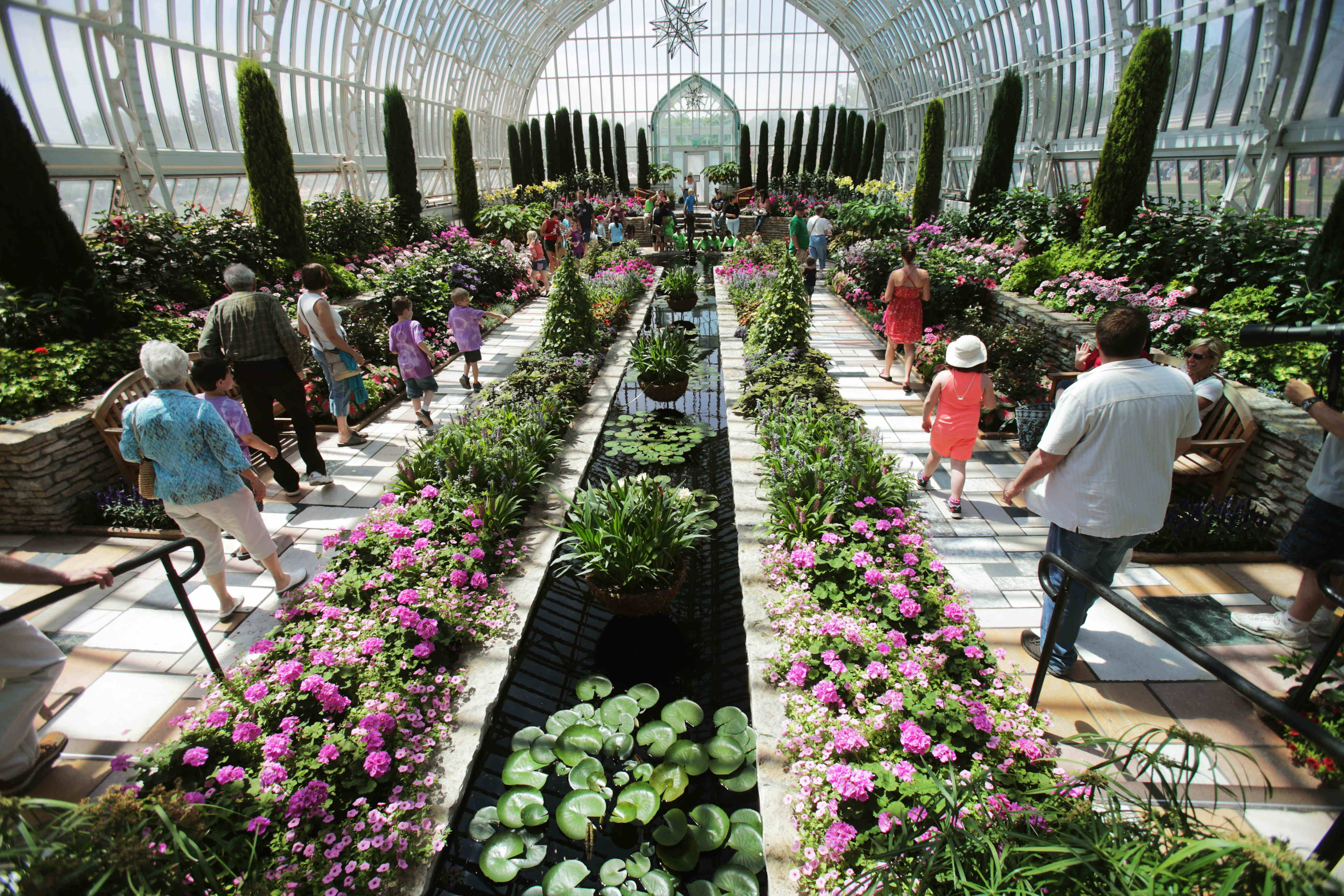 Visitors walk through the glassed-in Conservatory, which shows off tropical and other exotic plants year-round in a variety of indoor and outdoor gardens in St. Paul, Minn.