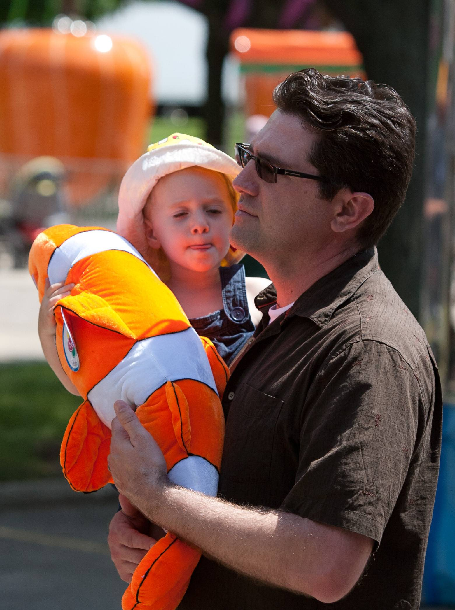 Doug Pelletier of Chicago holds his daughter Maeve Pelletier, 2, after winning a stuffed animal in a fire hose game during Eyes to the Sky in Lisle.