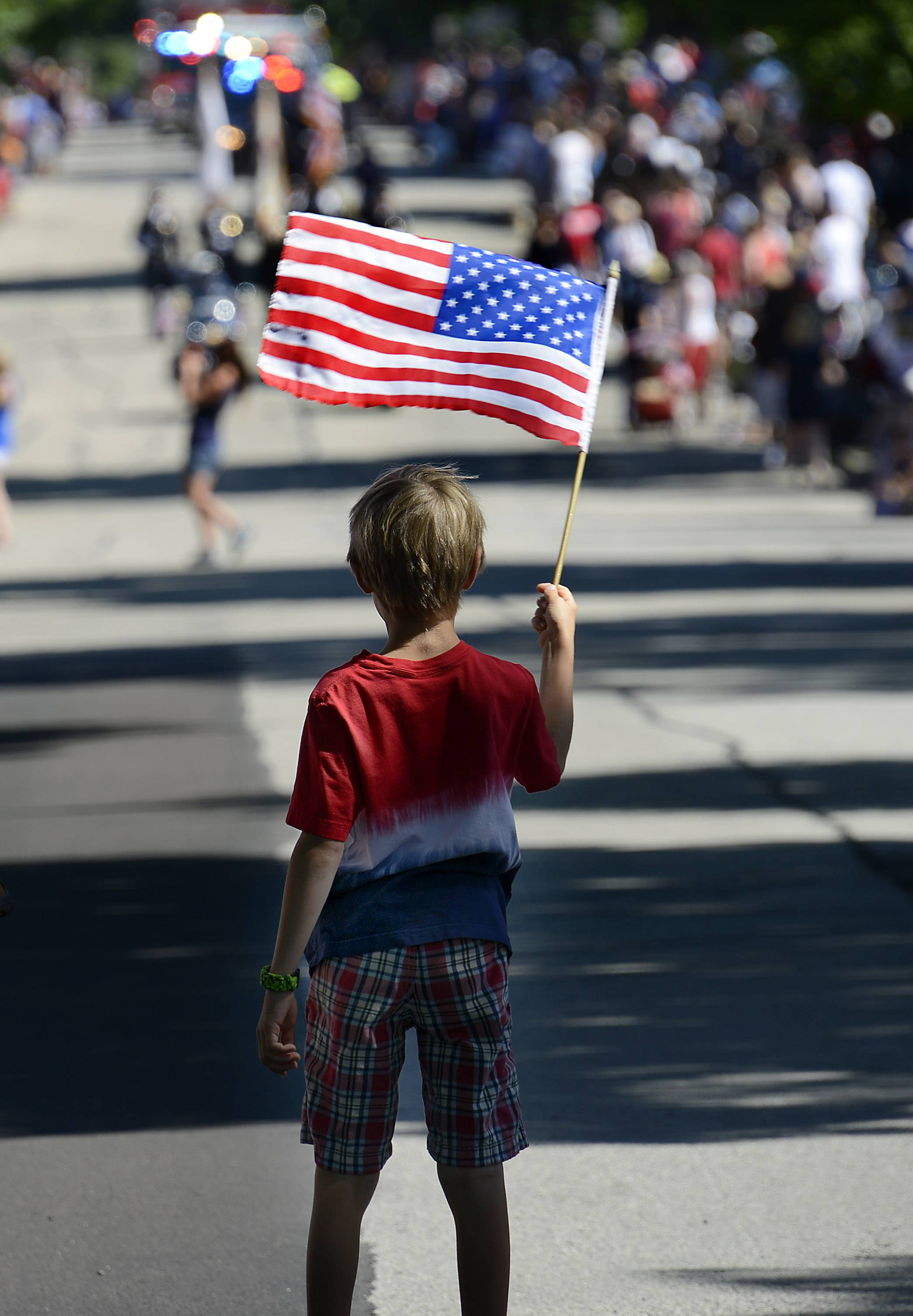 A parade fan waves his American flag in the middle of the street at the beginning of the Arlington Heights 4th of July parade on Friday.