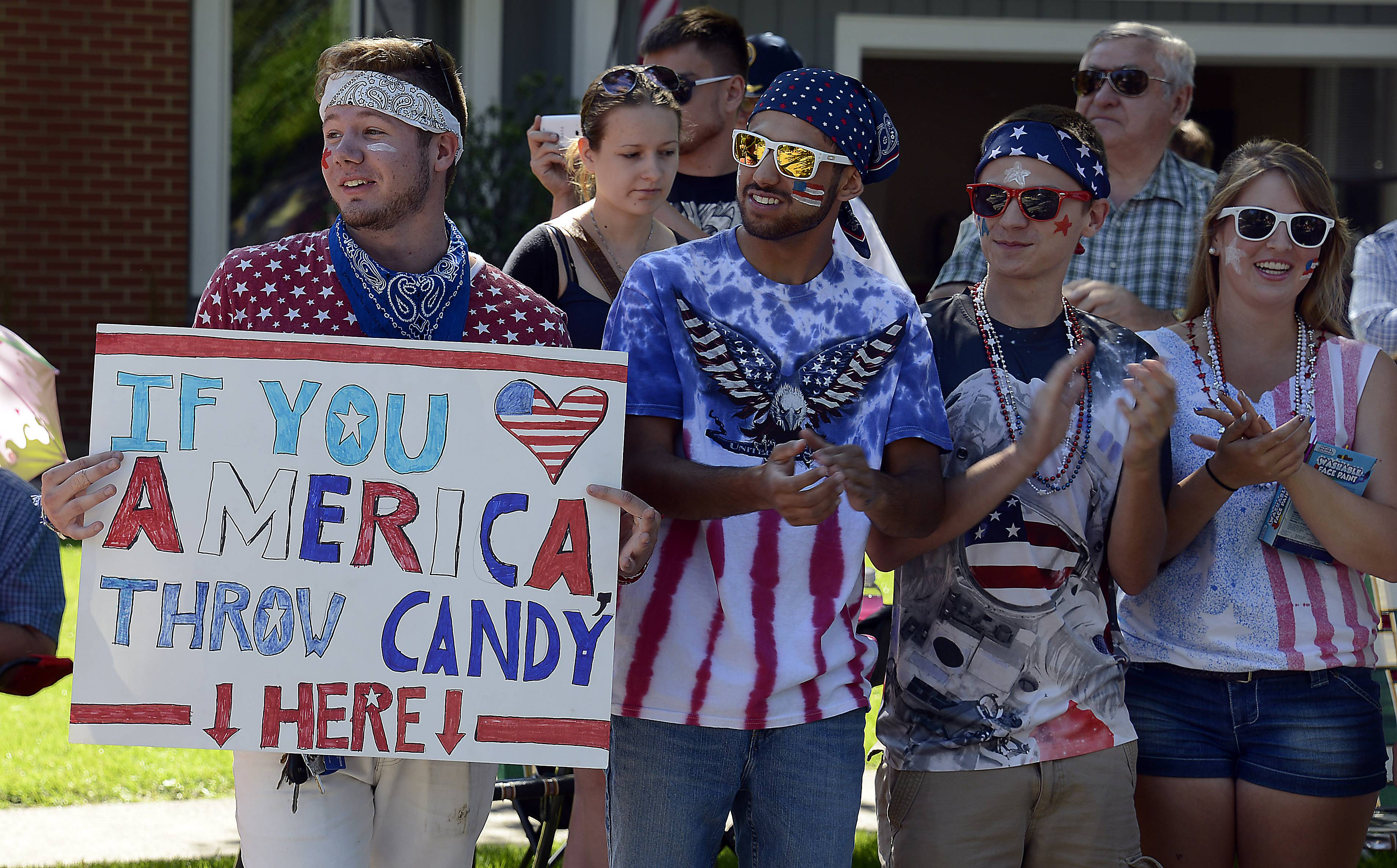 Michael Johnson and Jake Priester both of Prospect Heights try their best to get candy at the Arlington Heights 4th of July parade on Friday.