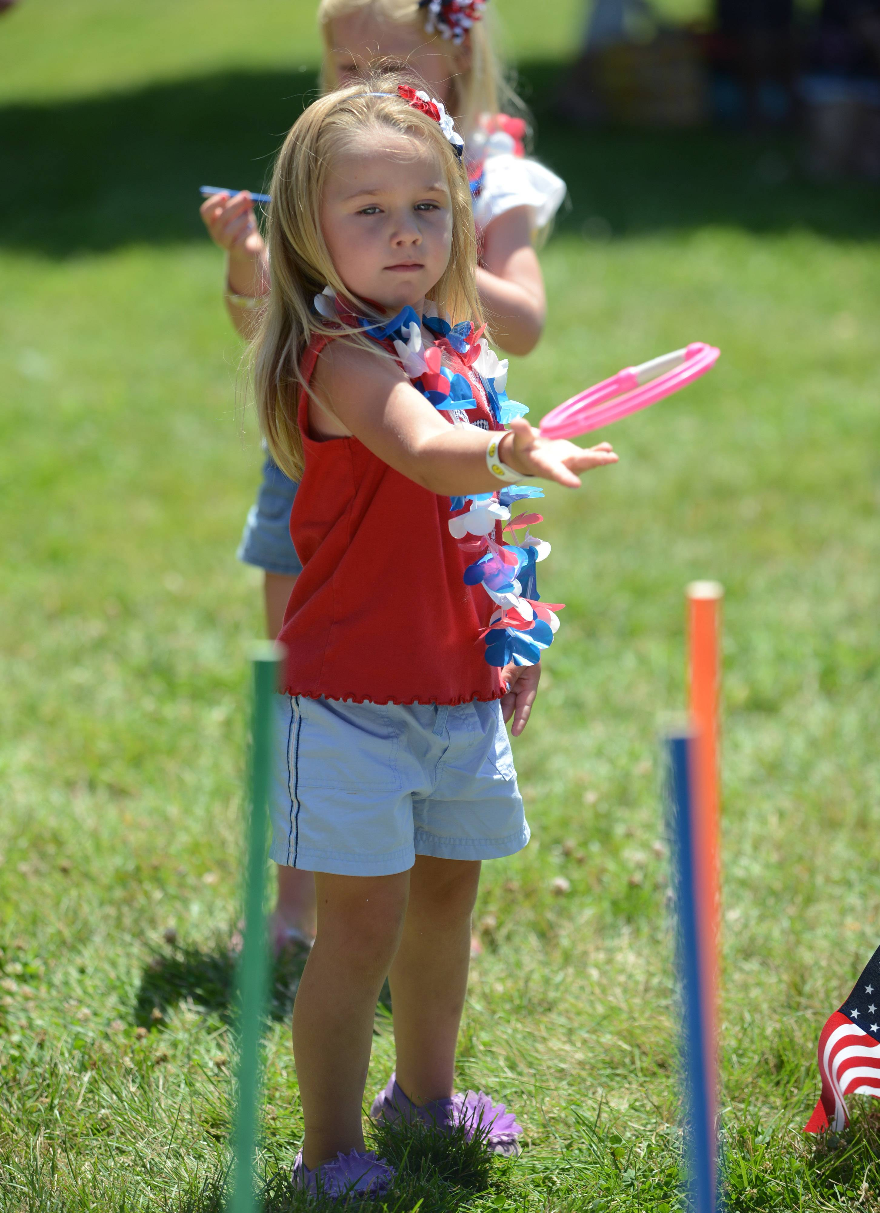 Elizabeth Krause, 4 of Lake Zurich, plays a ring toss game during the Fourth of July family day in Paulus Park Friday.