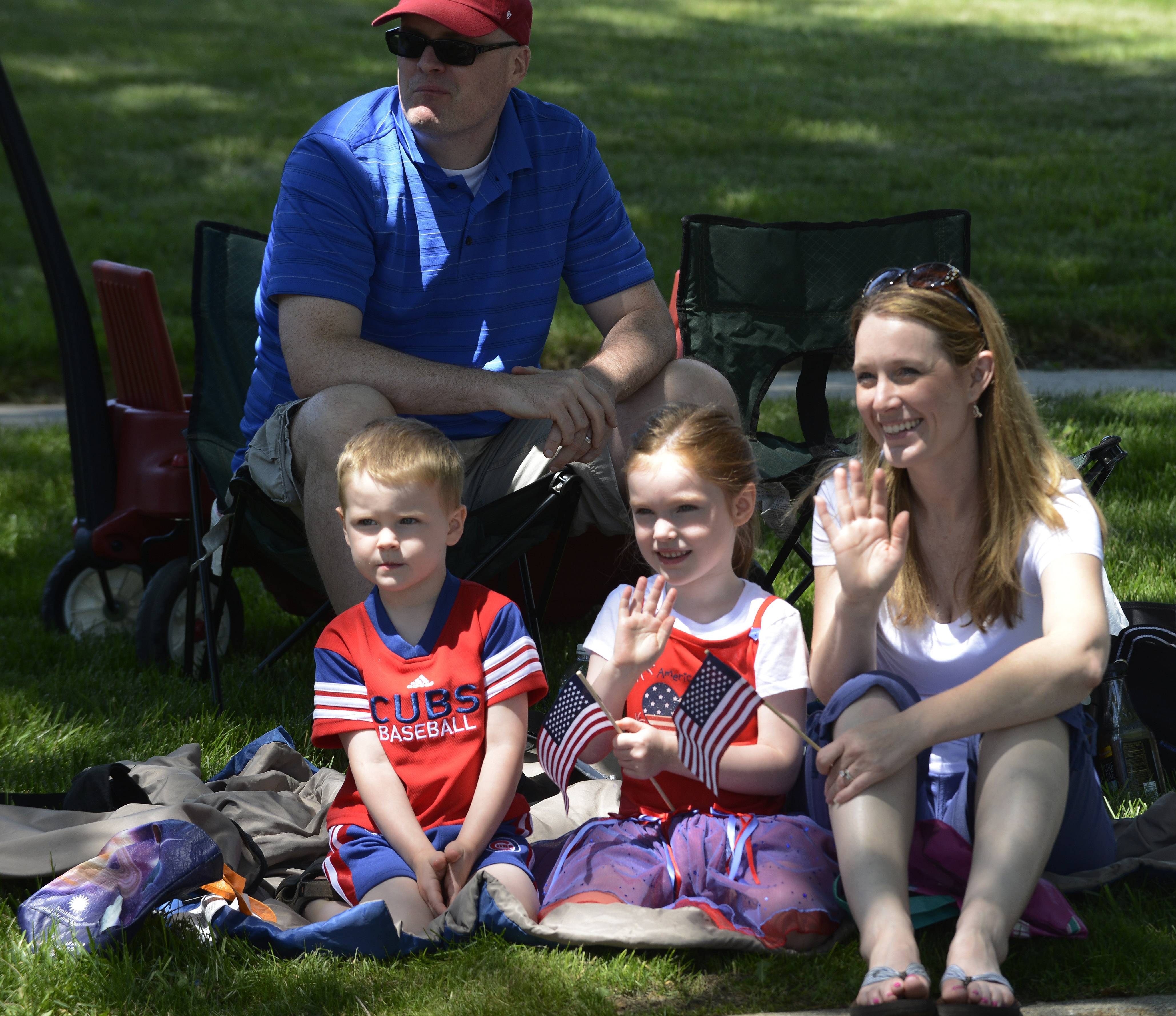 Jack Kuntz, 3, of Palatine, his sister, Mairead, 5, and parents, Jen and John watch the Rolling Meadows Fourth of July parade Friday.