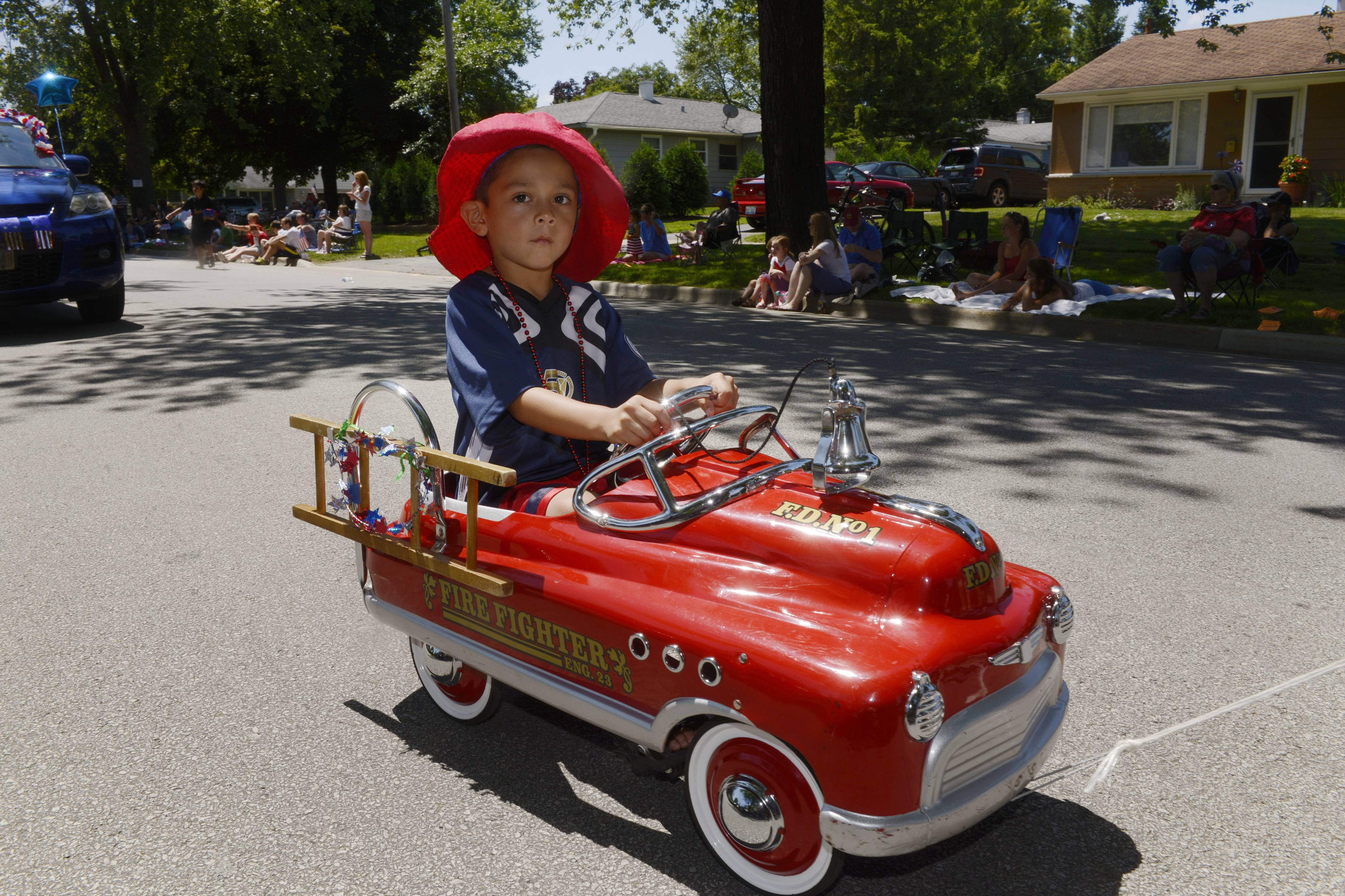 Damien Ortega, 6, of Rolling Meadows is being pulled in his fire engine during the Rolling Meadows Fourth of July parade Friday.
