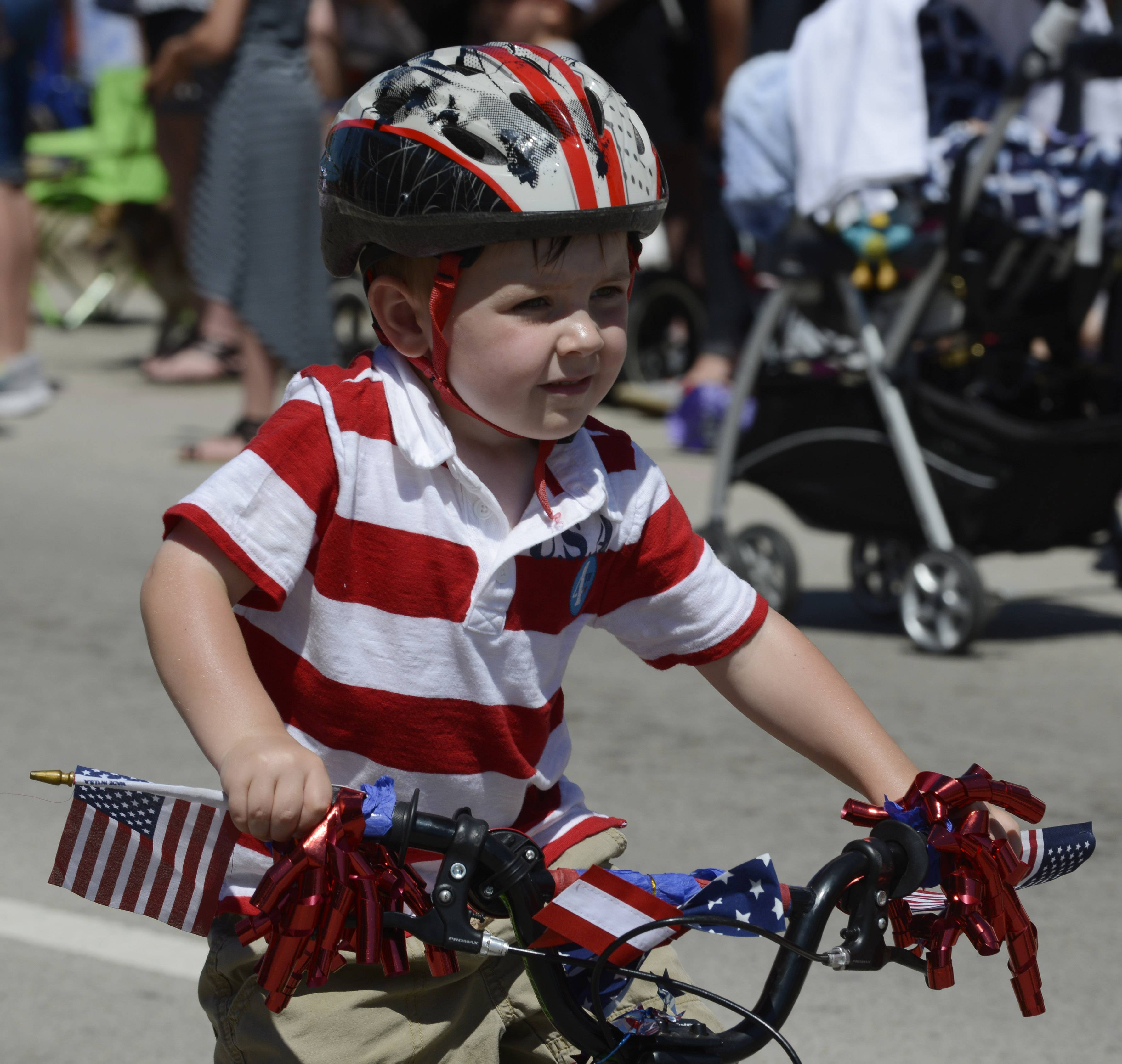 Ben Weibel, 3, of Barrington rides his bike in the Barrington Fourth of July parade Friday.