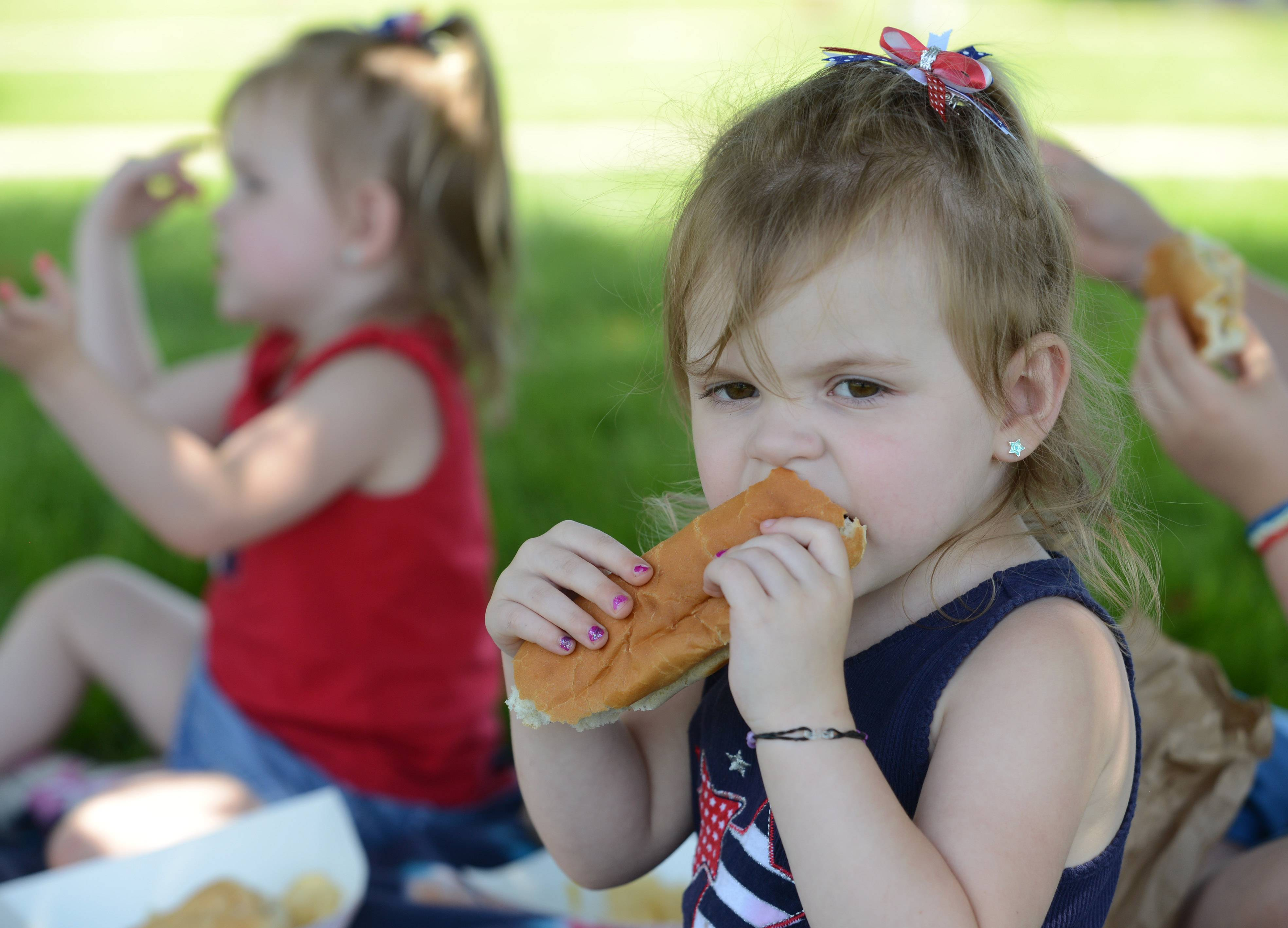 Madison Carr, age 3, digs into a hot dog along with her twin sister Sara, left, during Friday's Island Lake town picnic in Veterans Park.