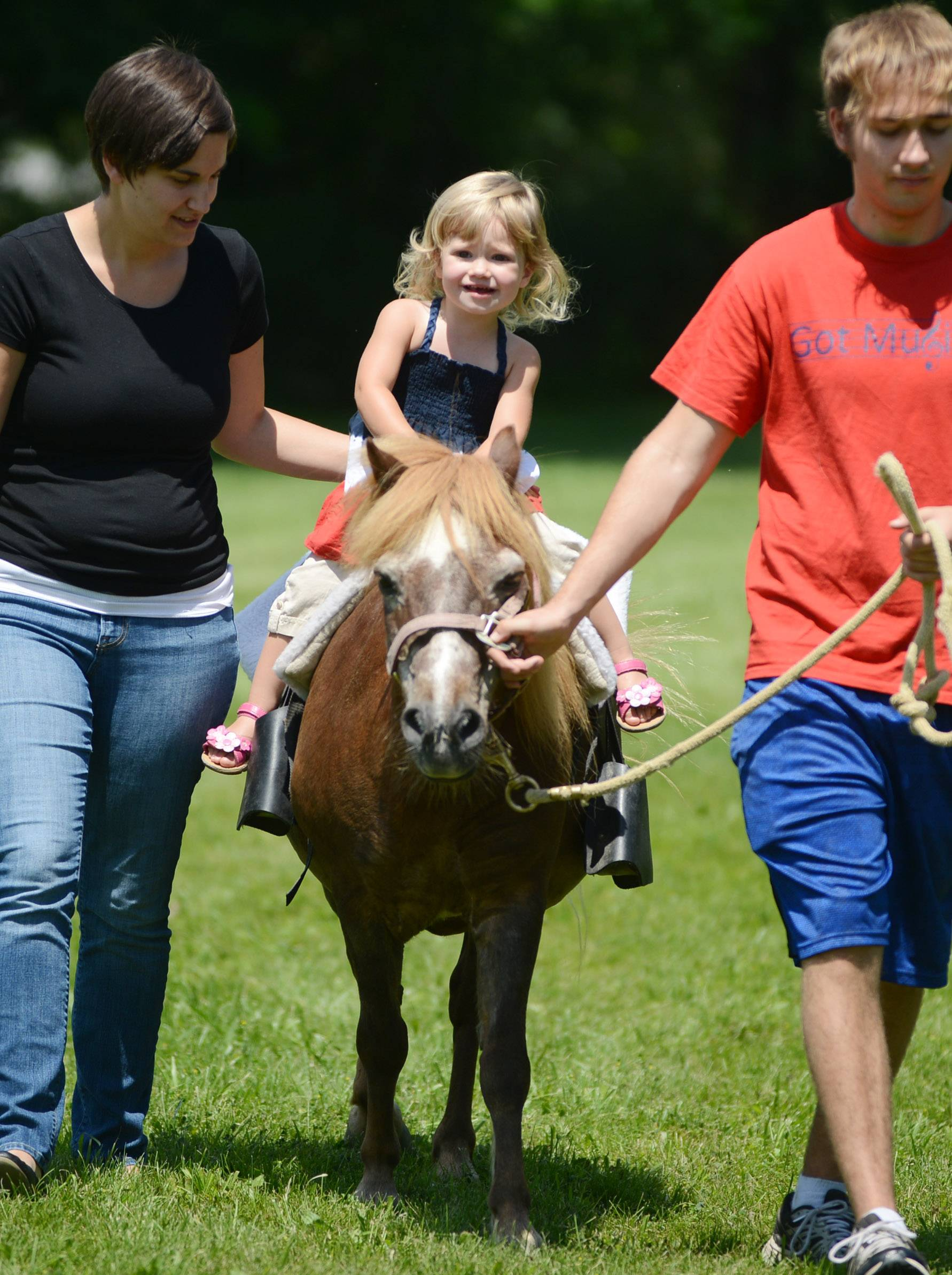Nicole Dodge, left of McHenry, walks alongside her daughter Ainsley Dodge, 2, during a pony ride Friday at Island Lake's town picnic in Veteran's Park.