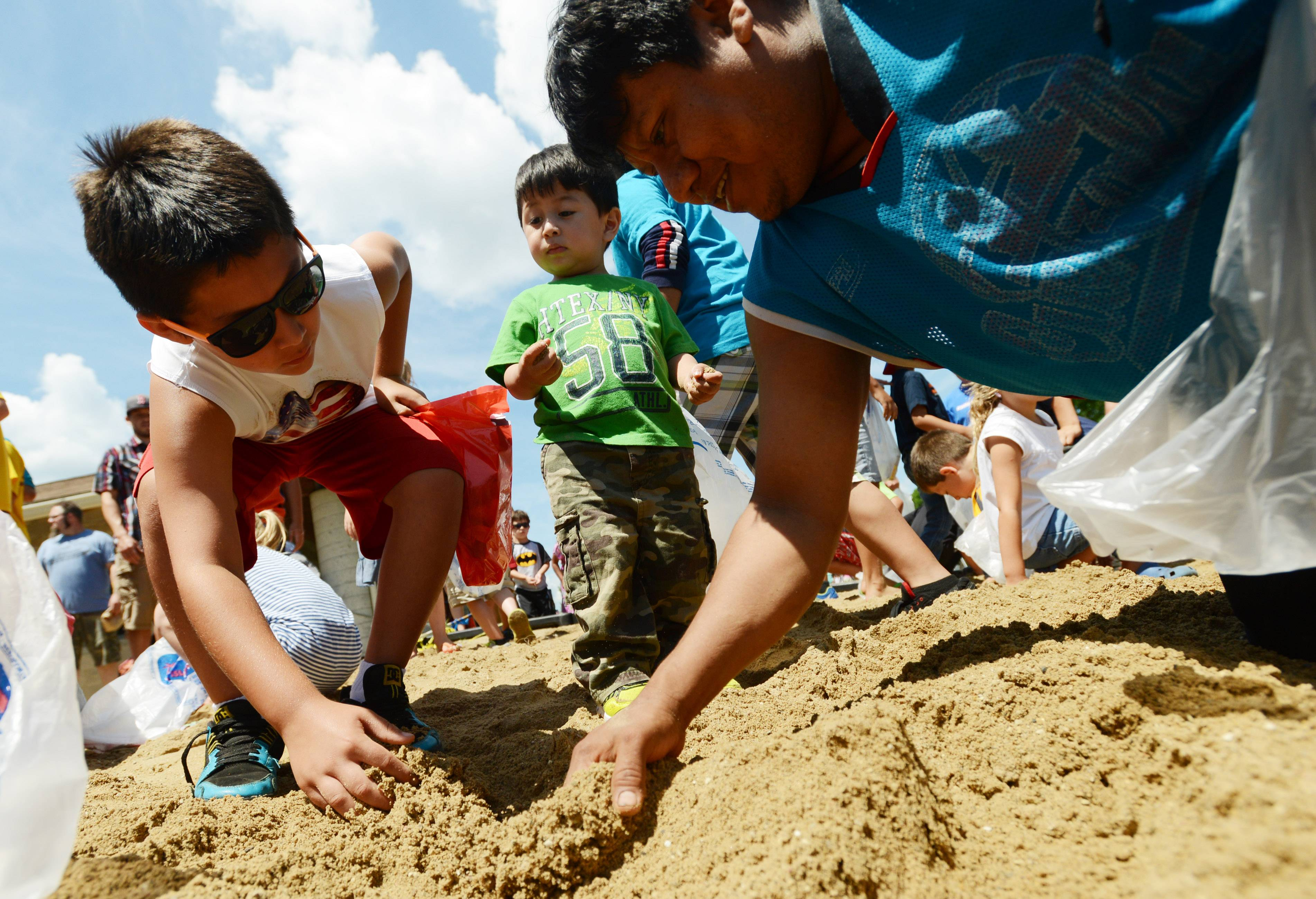 Two-year-old Ezequil Bello, center, watches as his dad Baltazar Bello, both of Island Lake, digs for goodies during a treasure hunt on the Veteran's Park beach in Island Lake Friday. The town held a community picnic follow its Fourth of July parade.