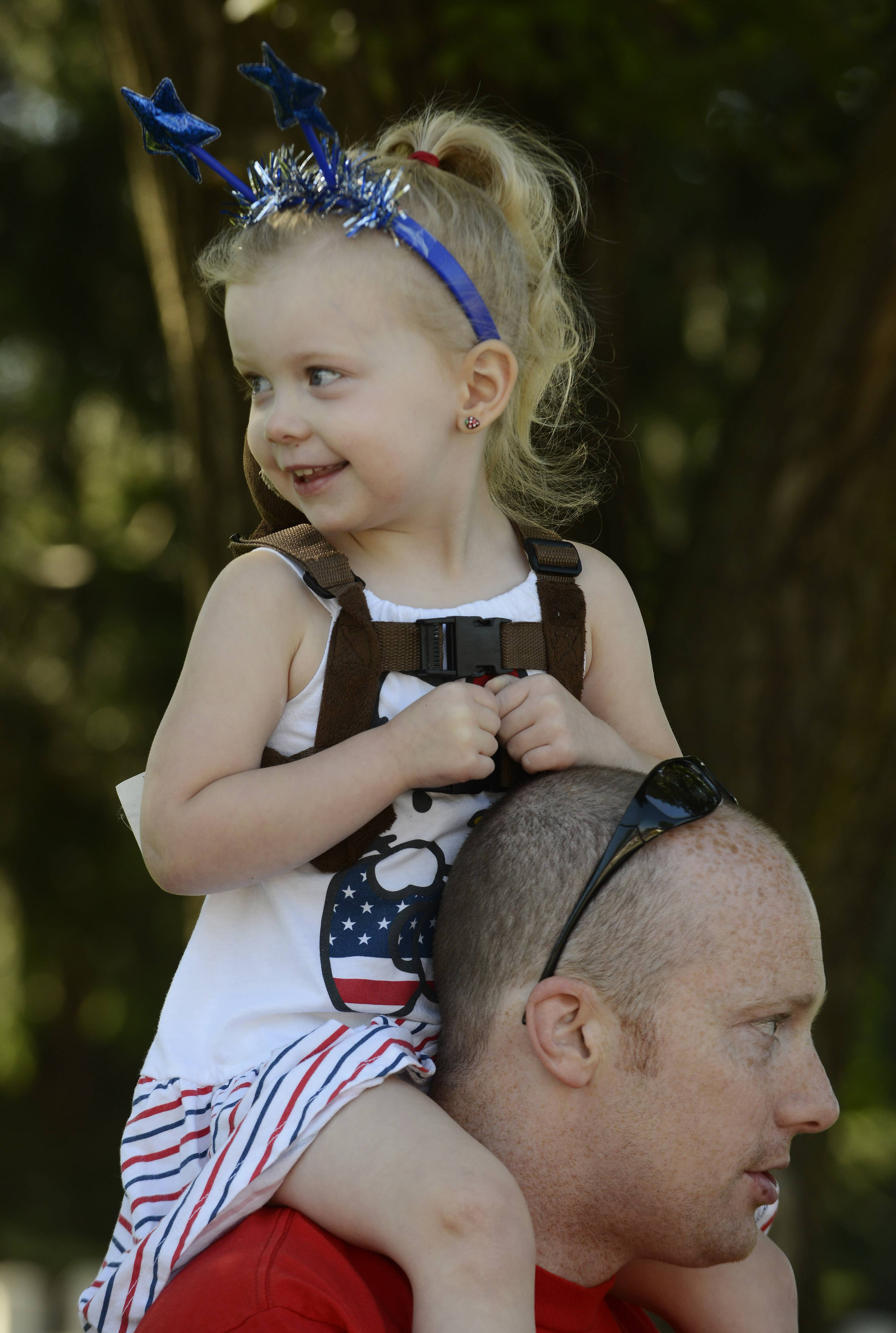 Elle Knoll, 3, of Hoffman Estates rides on the shoulders of her dad, David, during the Hoffman Estates Fourth of July parade Friday.