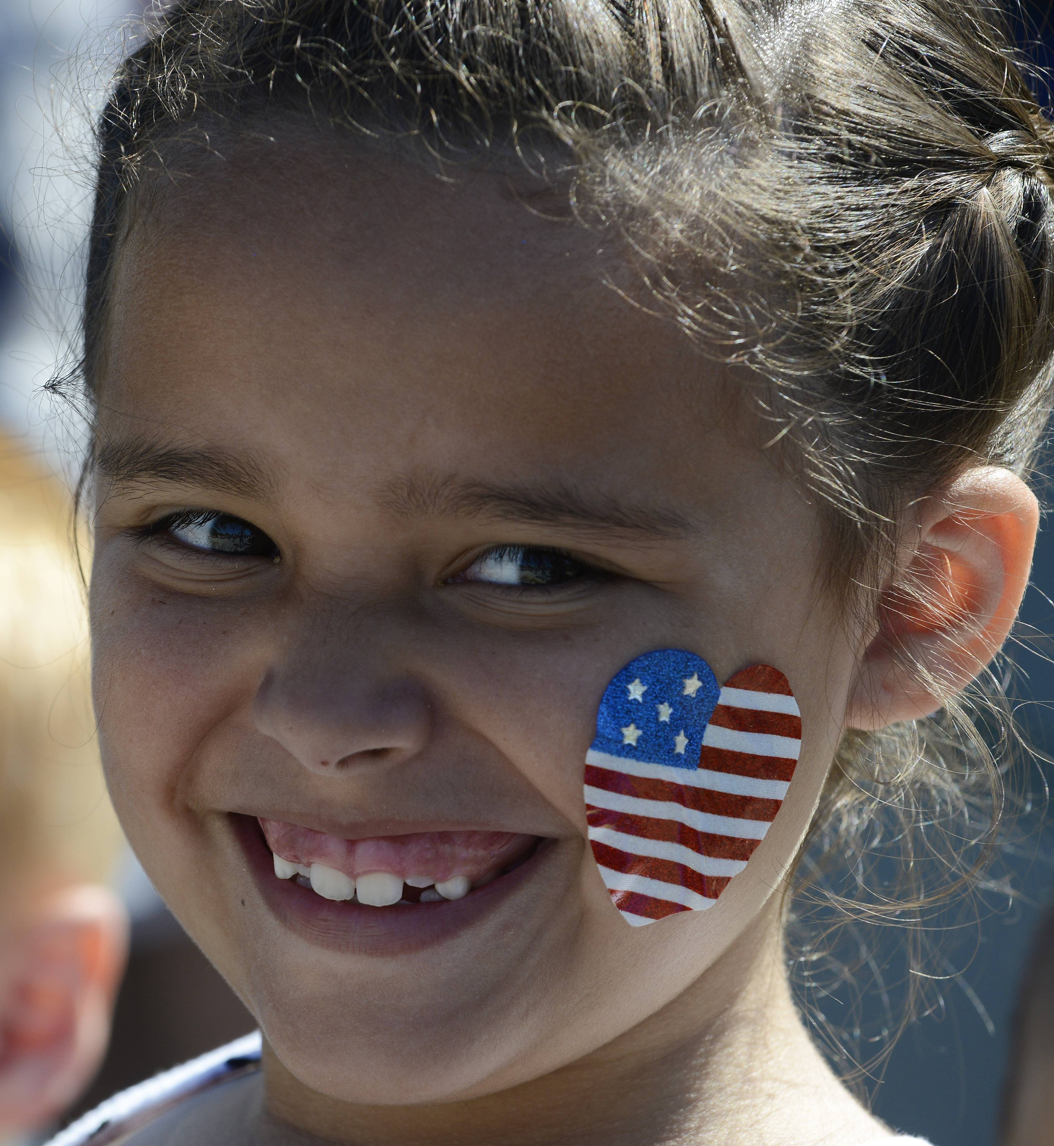 Kiley Quezada, 8, of Gilberts watches the Hoffman Estates Fourth of July parade Friday.