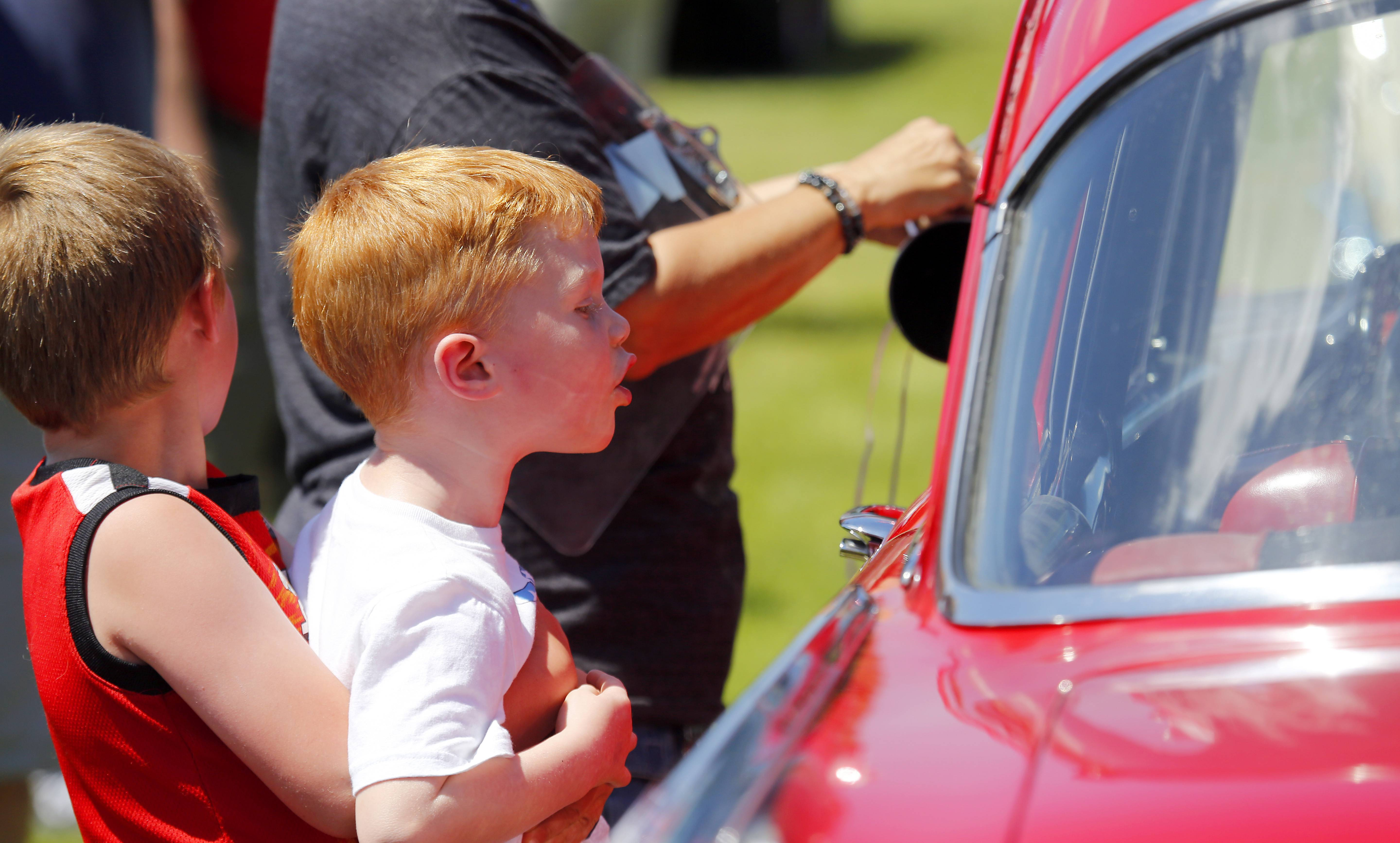 Matthew Pyrek, 6, gives his friend Carter Dustin, 4, both of Gilberts a lift to see into a 1957 Chevy 210 Bel Air during the Buick GS Club of America car show Friday in Sleepy Hollow.