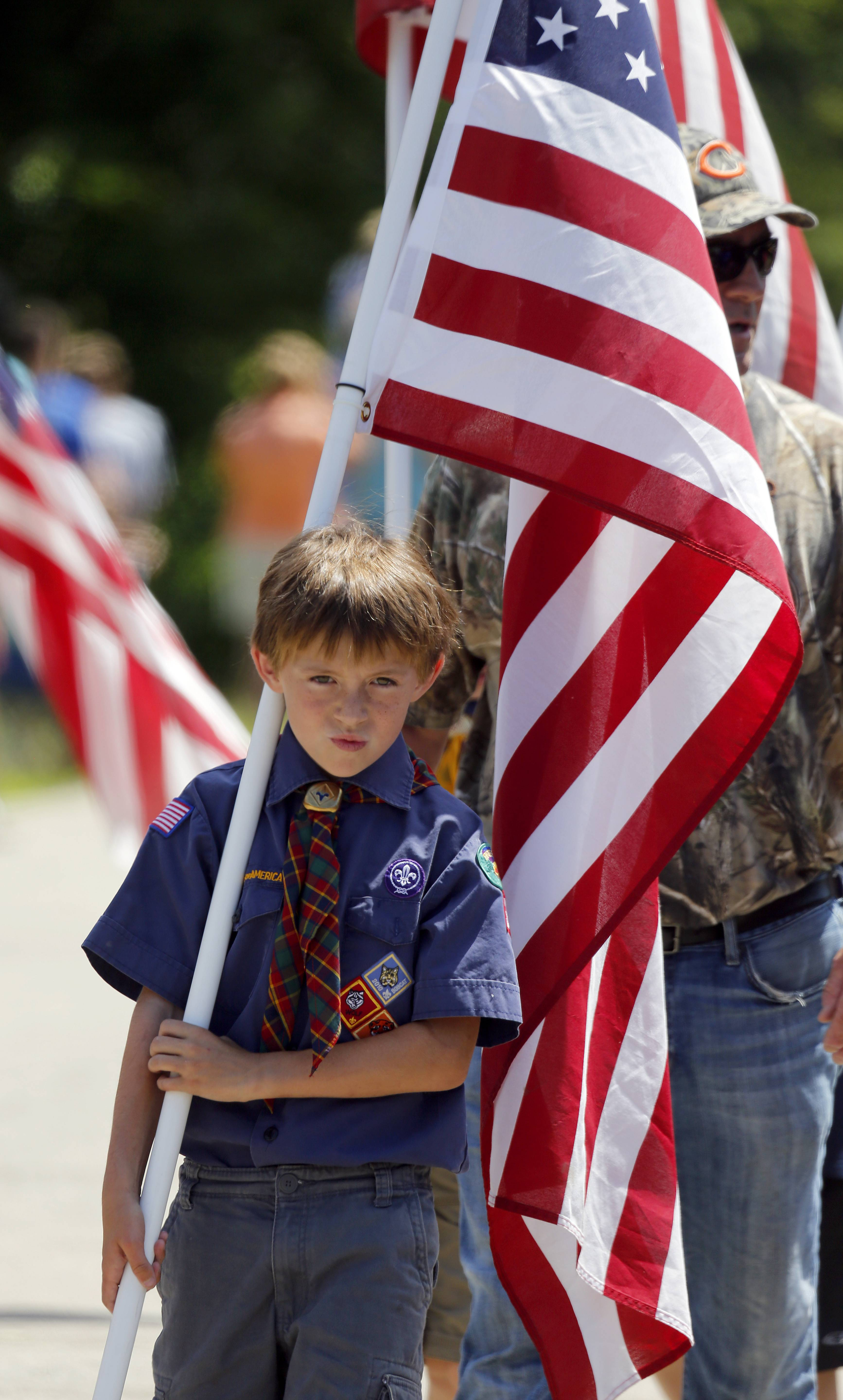 Bryce Pfeifer, 10, of Lake in the Hills and Webelos den 36 carries the flag during the Bill Ritchie Memorial Parade Fourth of July Parade Friday in Sleepy Hollow.
