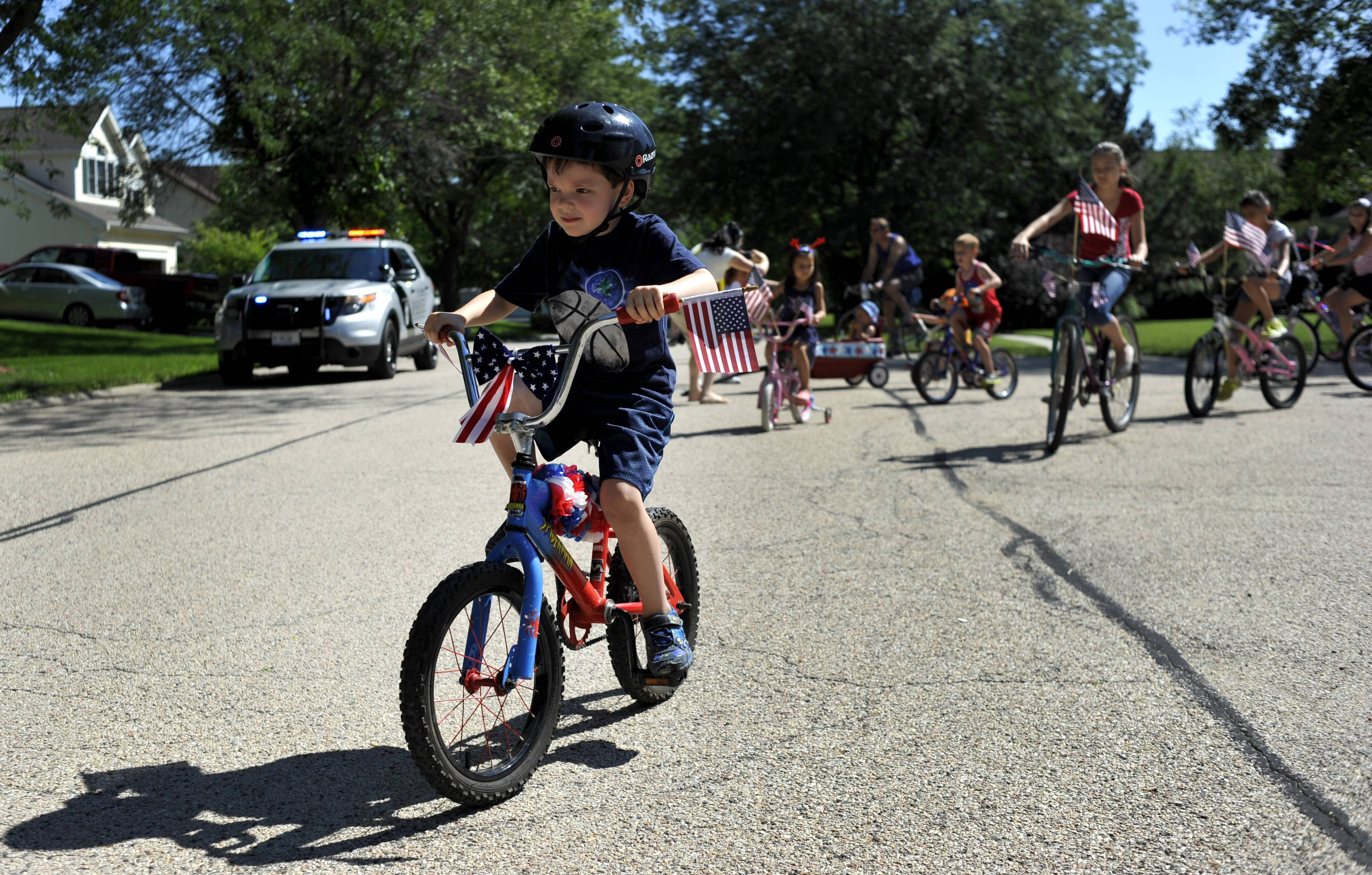 Ben Dawson, 5 of West Dundee rides his bike decorated with American flags at the Tartans/Hills neighborhood's annual Fourth of July kids' bike parade in West Dundee. The annual parade began in 1991 and is organized by the neighborhood, with Tim and Elizabeth Ward heading the organization of the event for the past few years.