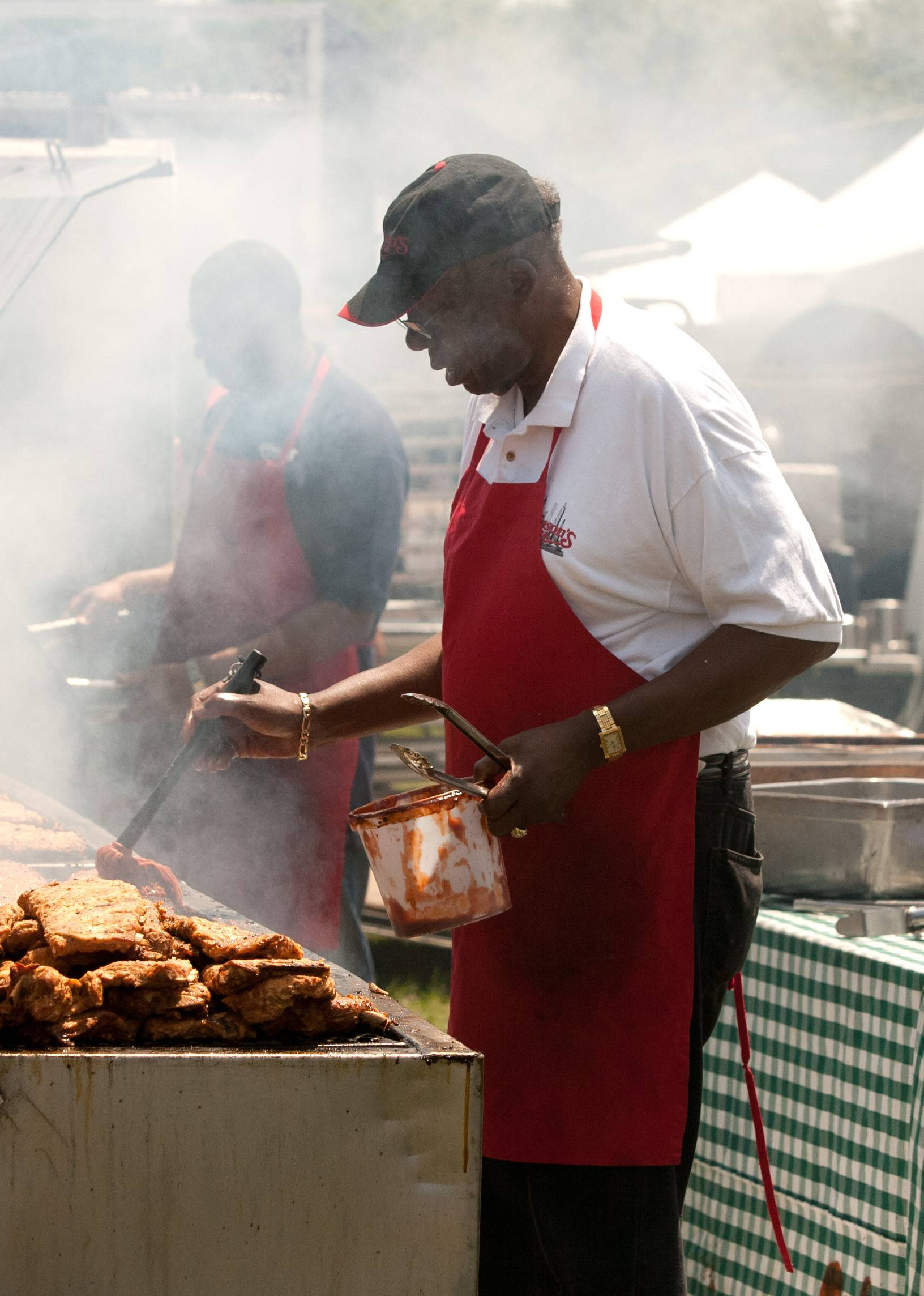 Charles Robinson, owner of Robinson's Ribs in Chicago and Oak Park sauces up several slabs of ribs during the Fourth of July Ribfest in Naperville