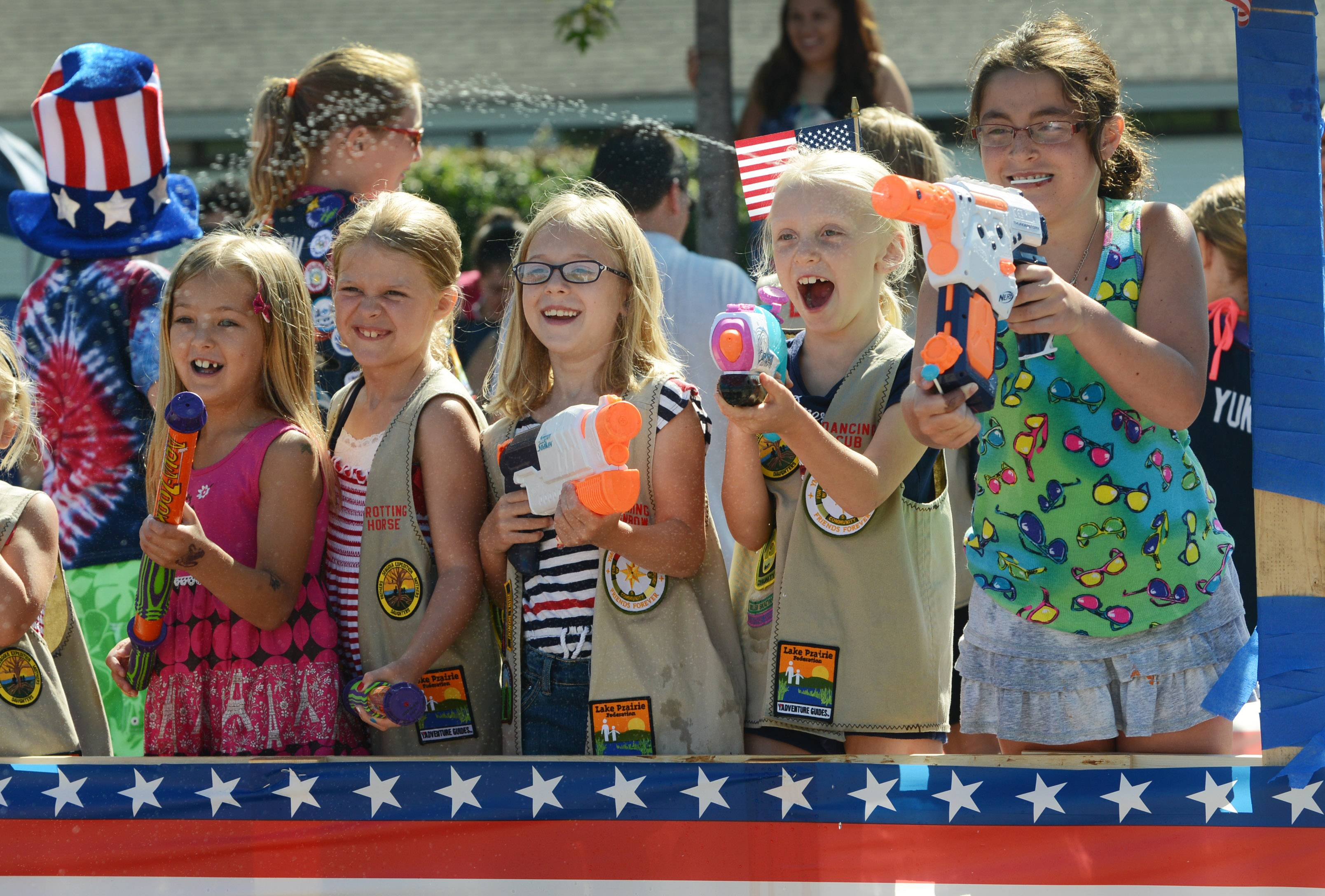 Members of the Lake Prairie Federation YMCA Guides & Princesses have fun spraying the crowd during Friday's Fourth of July parade in Vernon Hills.