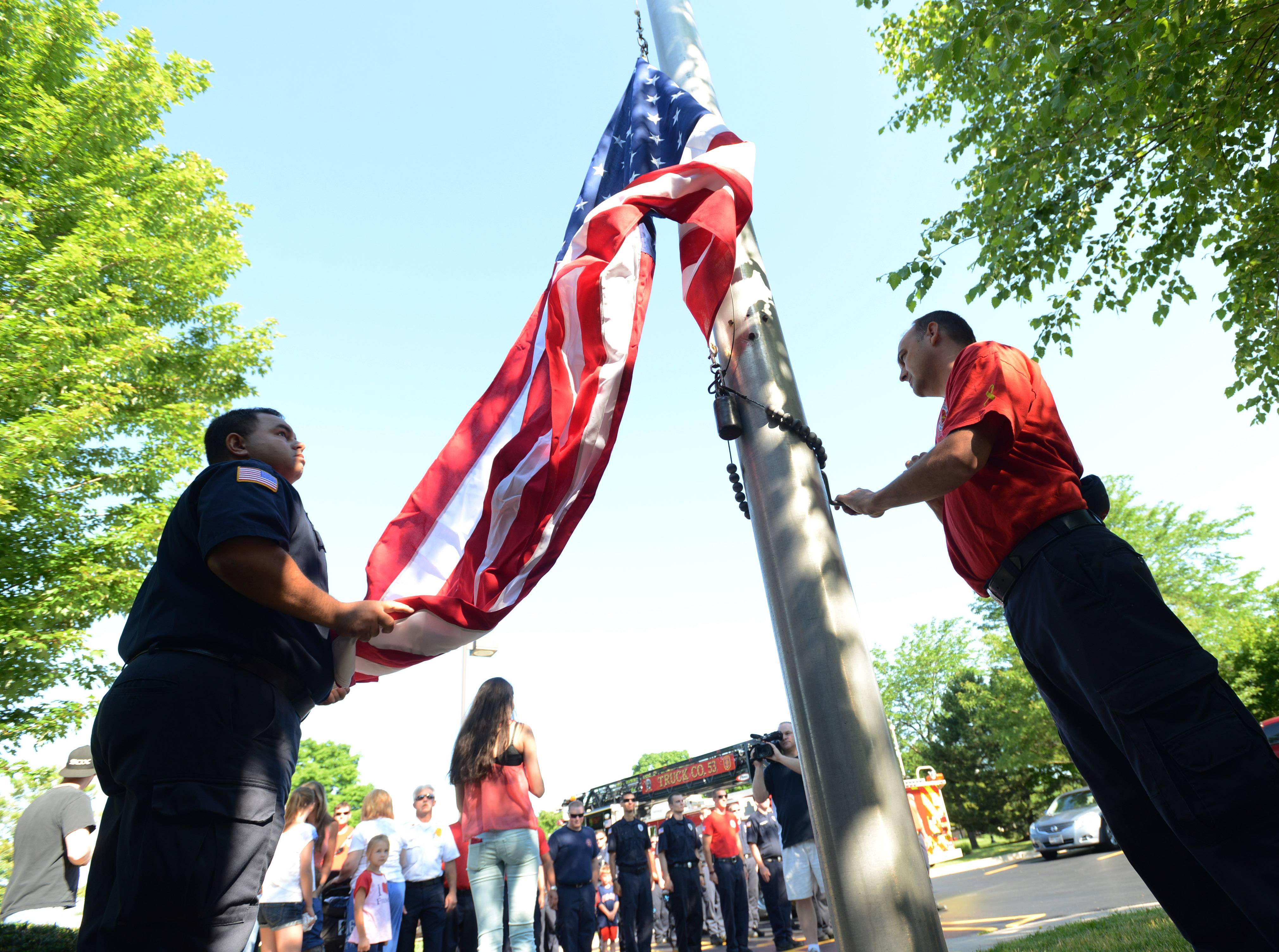 Countryside Fire Protection District firemedics Frank Faamasino, left, and John Sherwood raise the American Flag during a ceremony Friday at the start of the Vernon Hills Fourth of July parade.