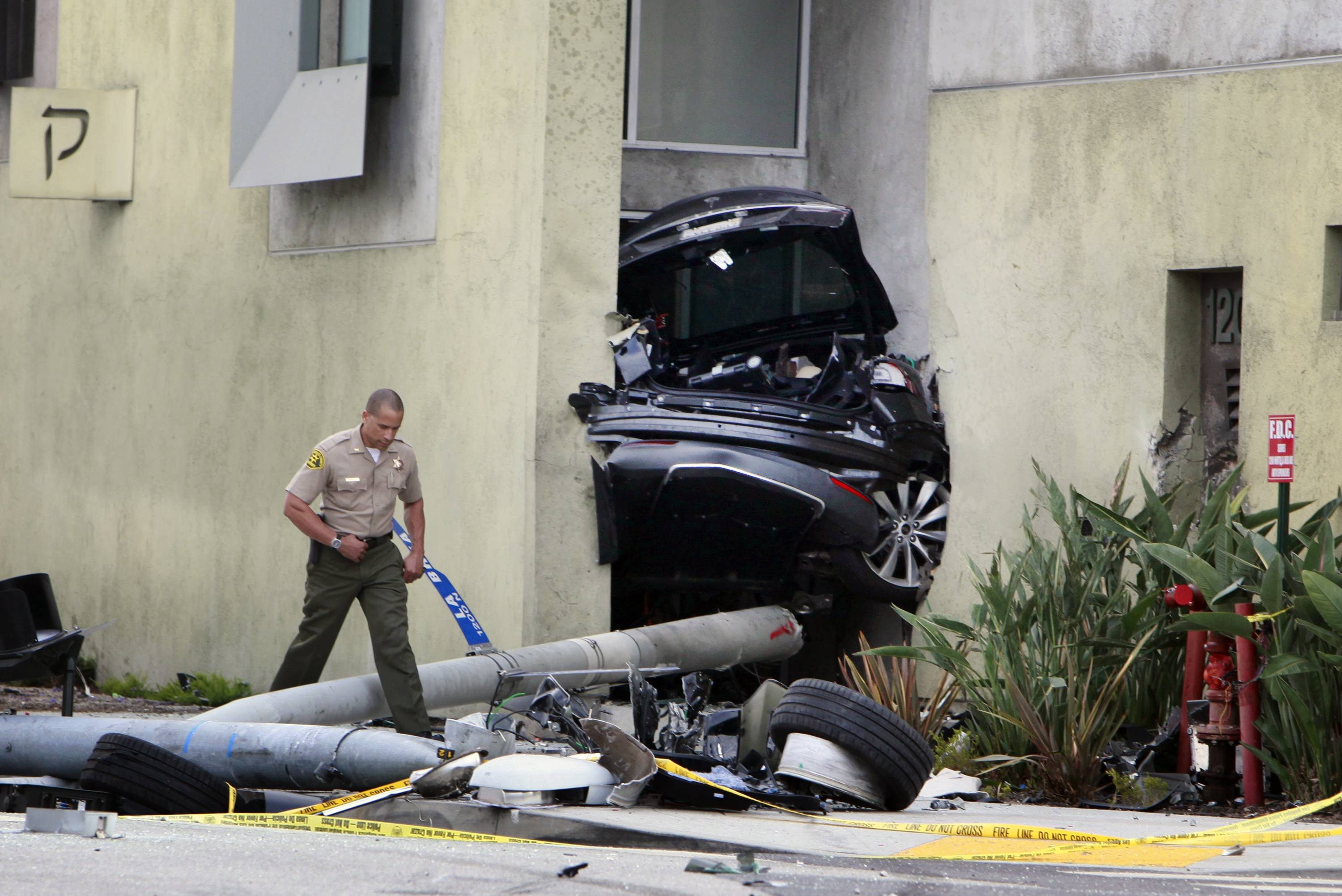 A Los Angeles County Sheriff's deputy walks past half the remains of a Tesla that wedged between two walls at Congregation Kol Ami synagogue in West Hollywood.