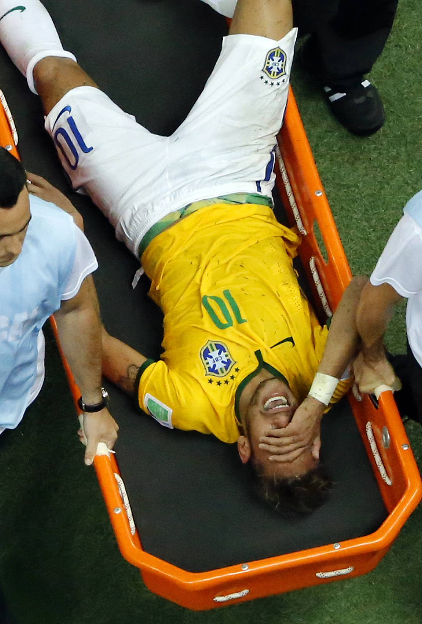 Brazil's Neymar is carried away after getting injured during the World Cup quarterfinal soccer match between Brazil and Colombia at the Arena Castelao in Fortaleza, Brazil, Friday, July 4, 2014. Brazil's team doctor says Neymar will miss the rest of the World Cup after breaking a vertebrae during the team's quarterfinal win over Colombia.