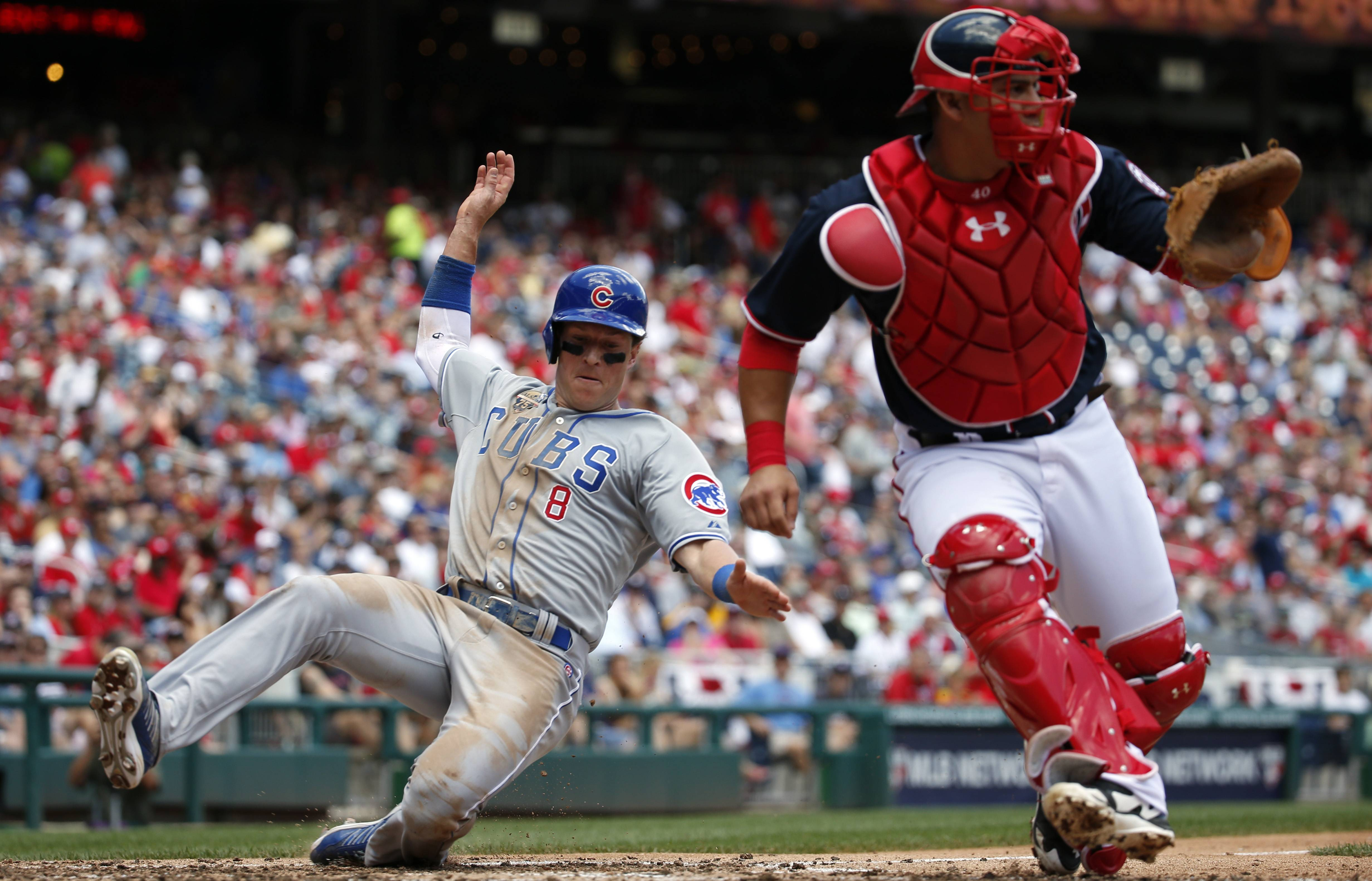 The Cubs' Chris Coghlan slides safely into home as Nationals catcher Wilson Ramos waits for the throw during the fifth inning Friday in Washington, D.C.