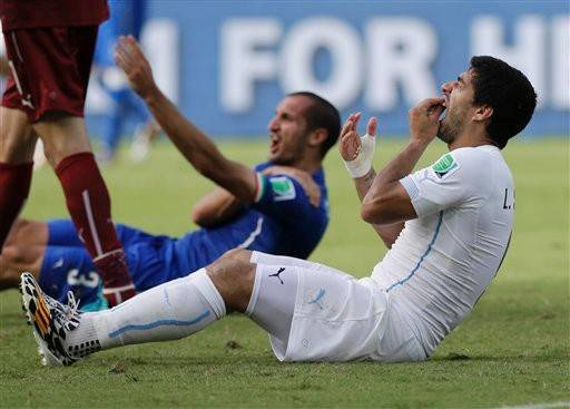 Uruguay's Luis Suarez bit Italy's Giorgio Chiellini's shoulder during the group D World Cup soccer match between Italy and Uruguay at the Arena das Dunas in Natal, Brazil, Tuesday, June 24, 2014.