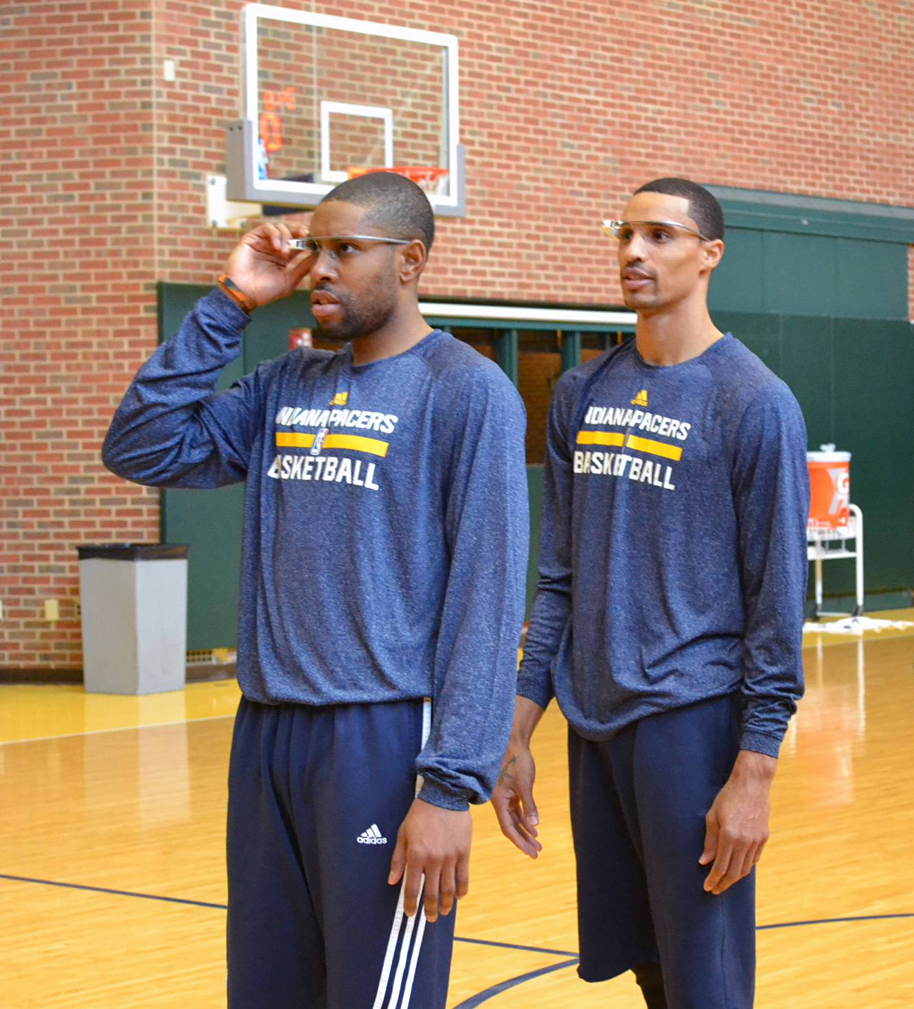 In this March 25, 2014 photo provided by Pacers.com, Indiana Pacers basketball players C.J. Watson, left, George Hill, center, and Lavoy Allen, at right back to camera, wear Google glasses during practice at Bankers Life Fieldhouse in Indianapolis. Google Glass is slowly becoming more common in sports as teams and broadcasters try to bring fans closer to the action.