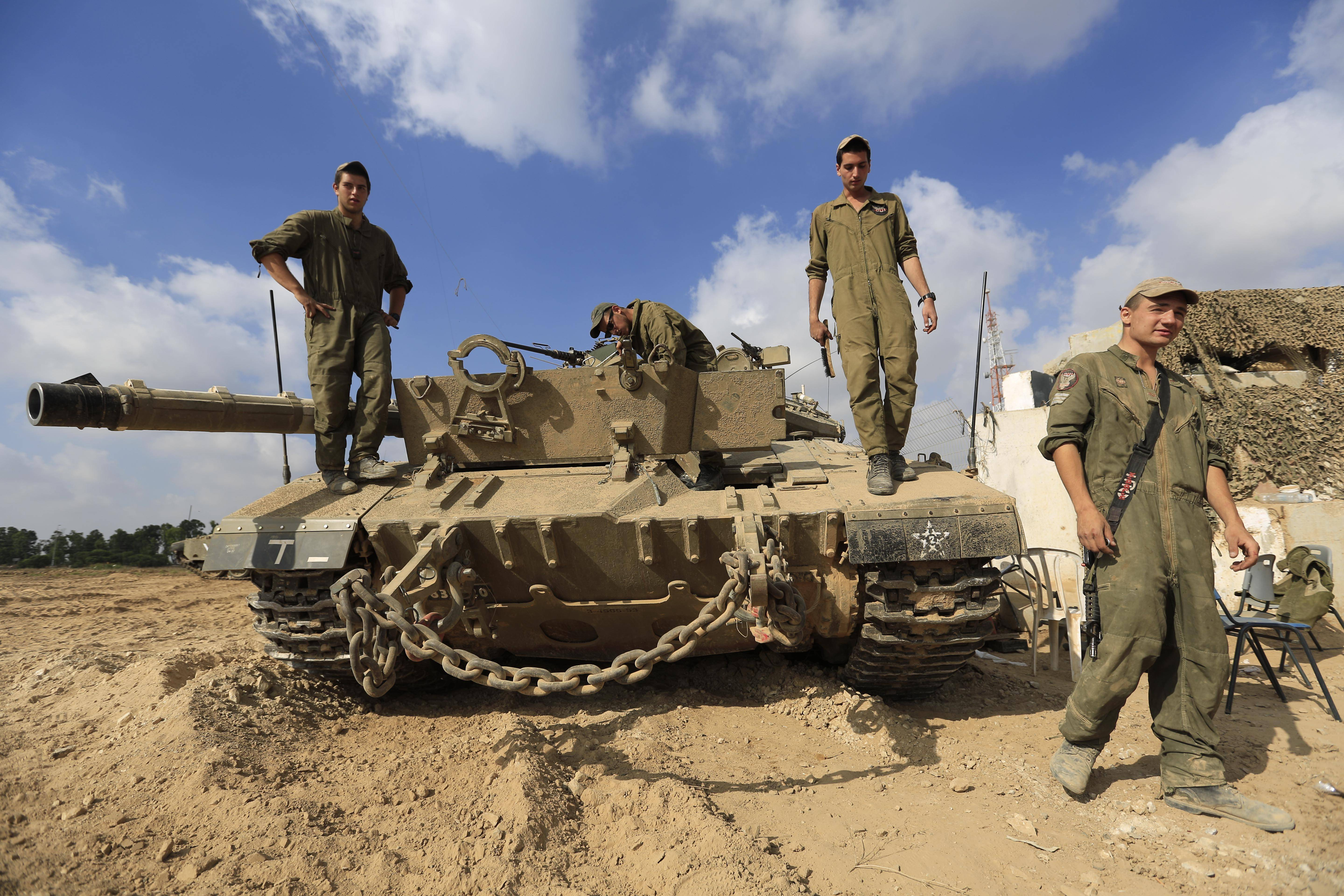 Associated Press Israeli soldiers and armor gather Saturday near the Israel and Gaza Strip border.