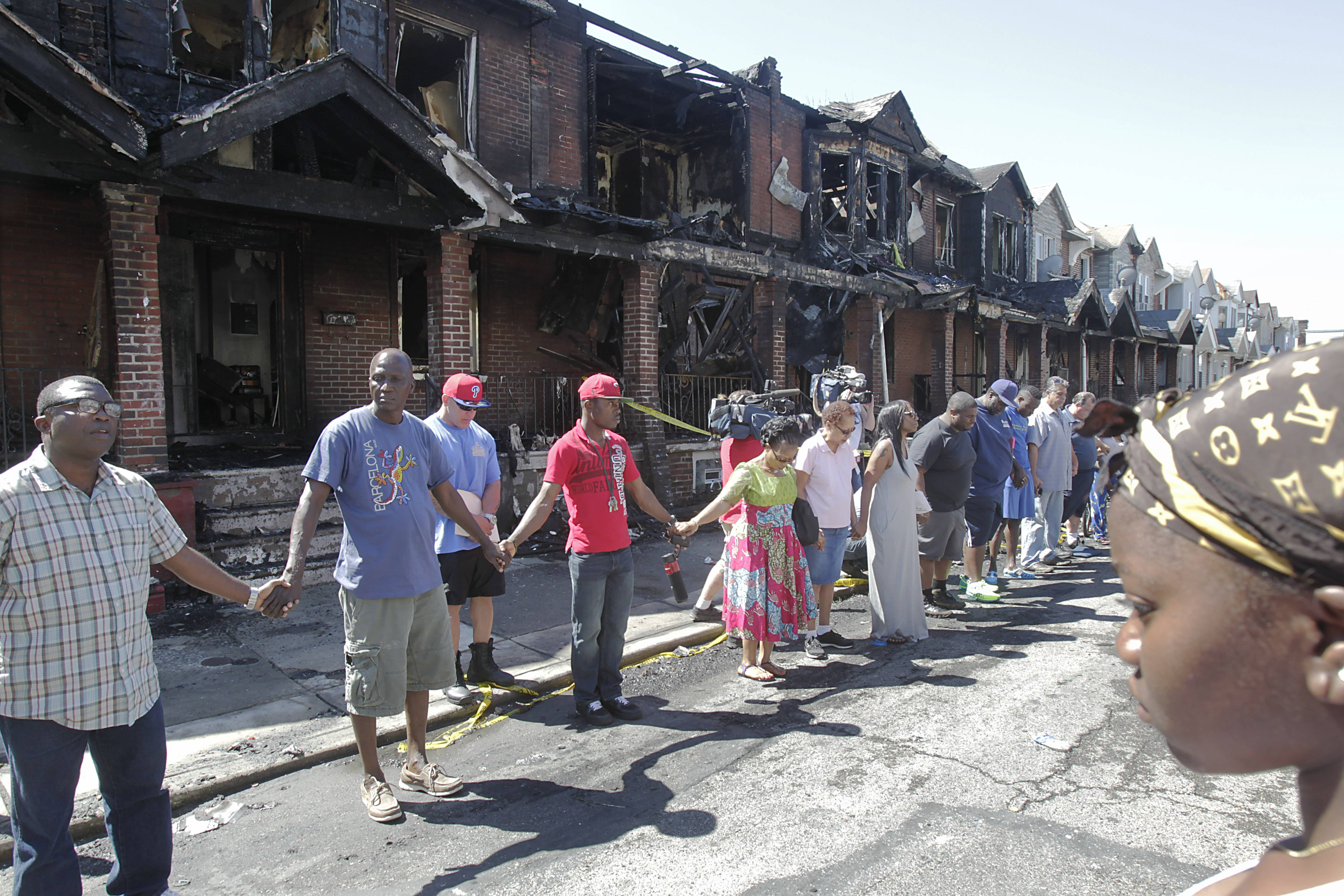 Friends of the community form a circle in front of burned row houses, and pray for people who were affected the fire Saturday.